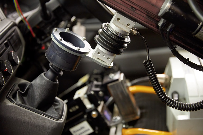 Robot driver attached to vehicle gear stick