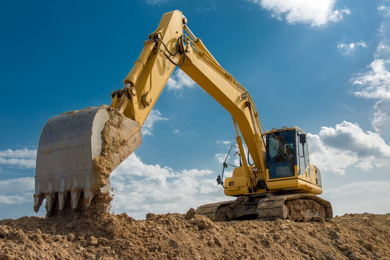 Excavator dropping soil on construction site