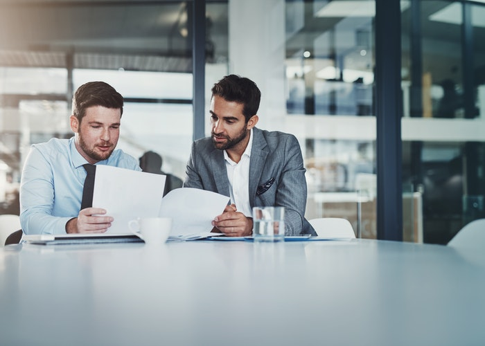 To mænd læser papir på bord