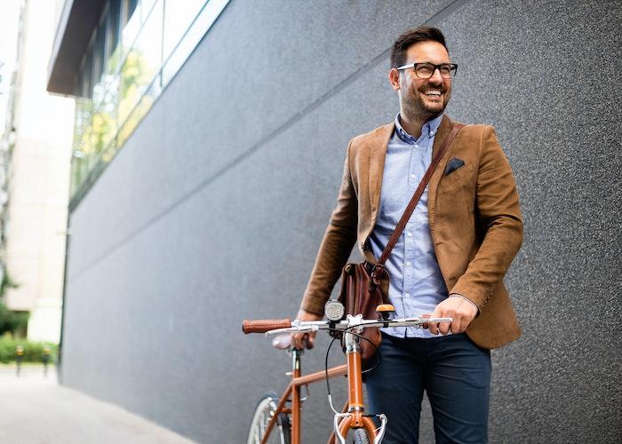 Mand med cykel ved kontorbygning