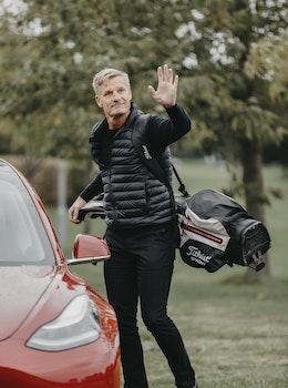 Mand med golftaske og tesla