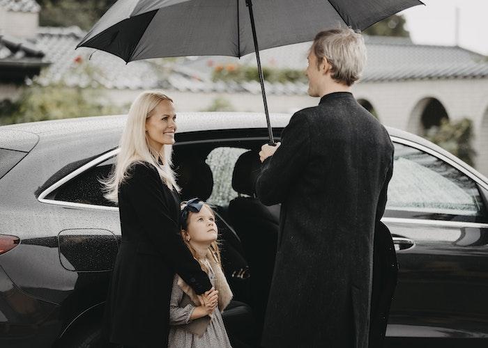 Familie ved bil i regnvejr