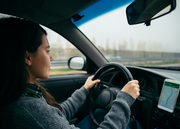 Kvinde kører bil med gps