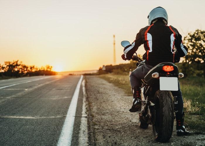 mand på motorcykel ved solnedgang
