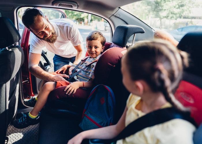 Far spænder børn fast i autostole