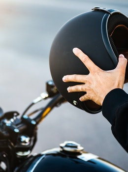 Mand på motorcykel med hjelm i hånden