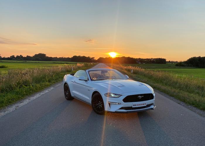 Hvid Ford Mustang i solnedgang
