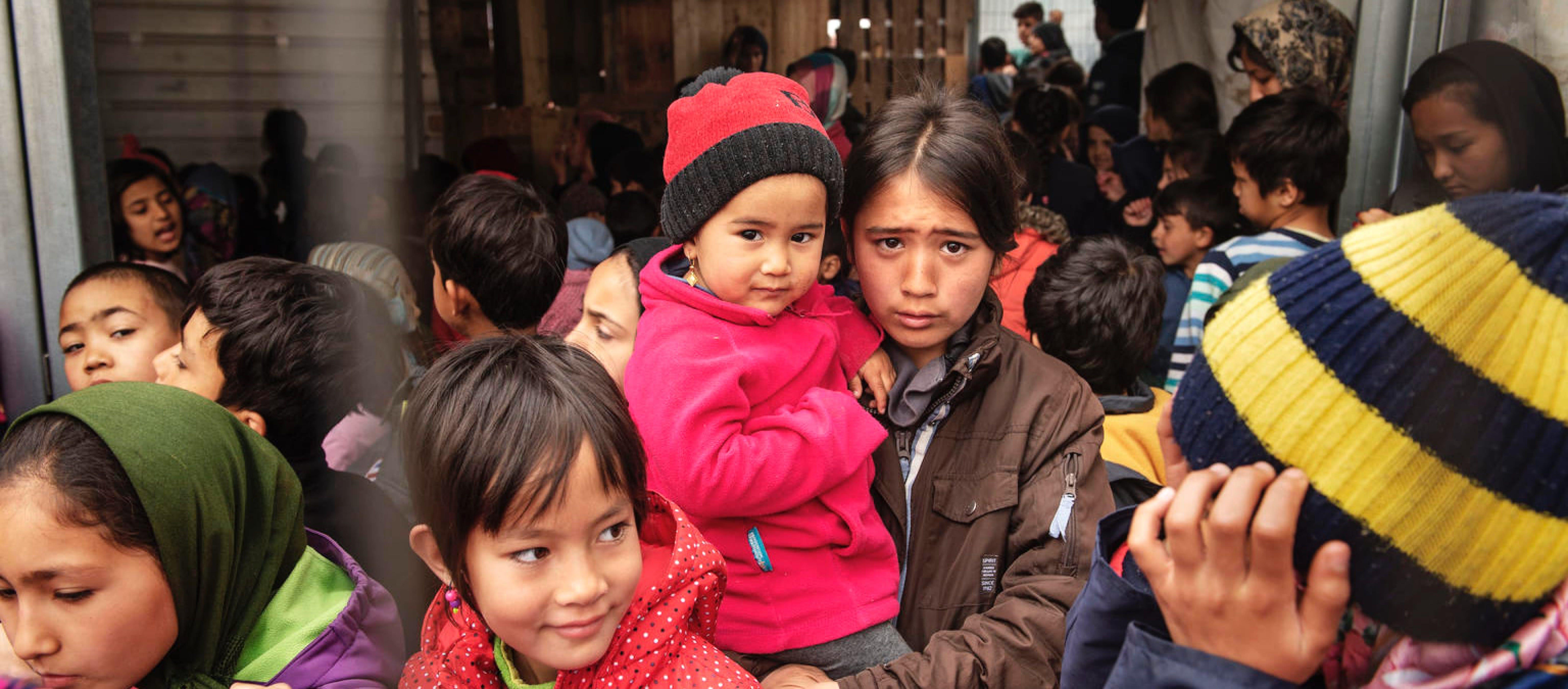 Bambini migranti in fila per un succo di frutta sull'isola di Lesbo, in Grecia.