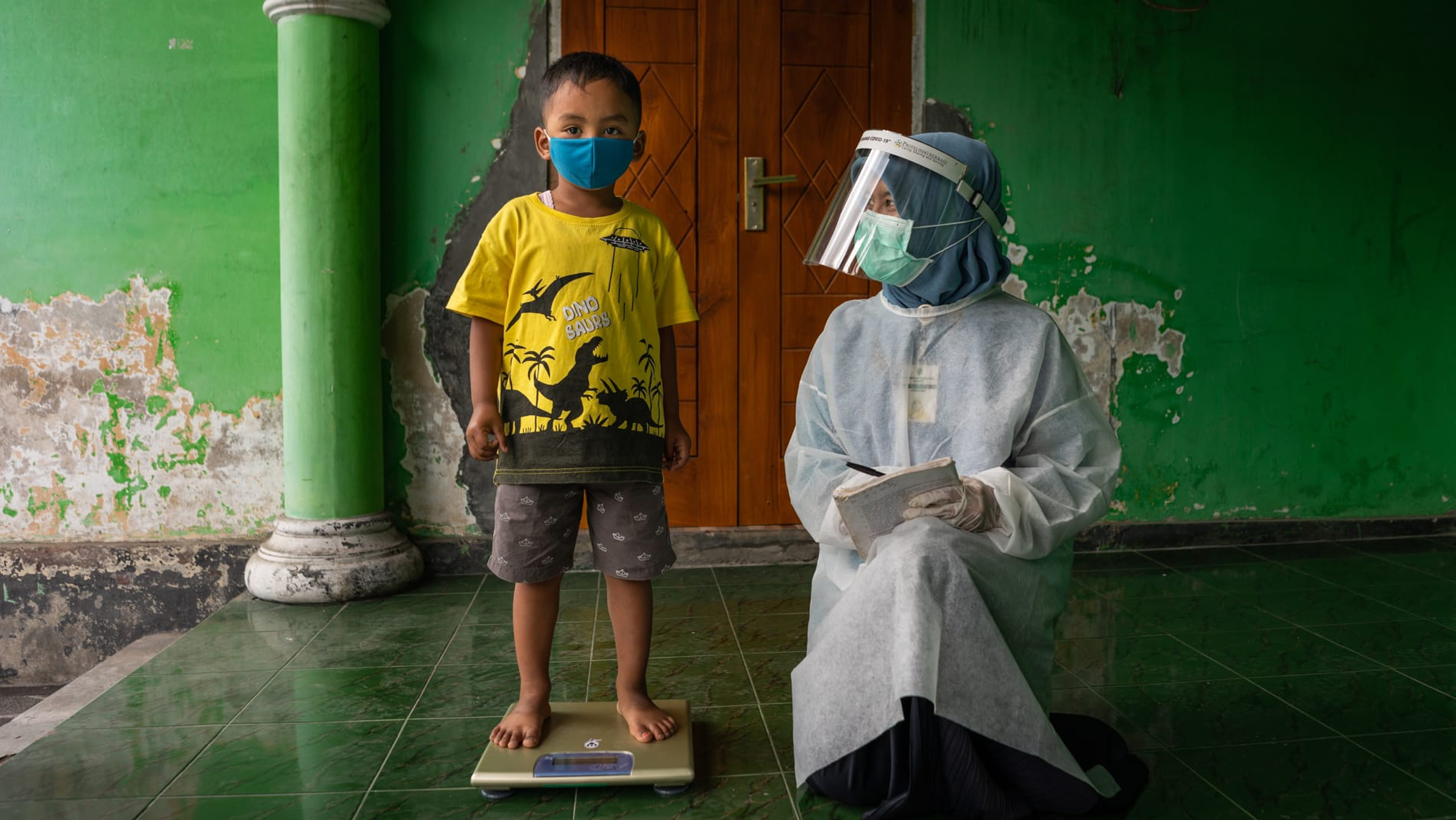 Un bambino viene pesato in una postazione sanitaria nel villaggio di Sidorejo, in Indonesia