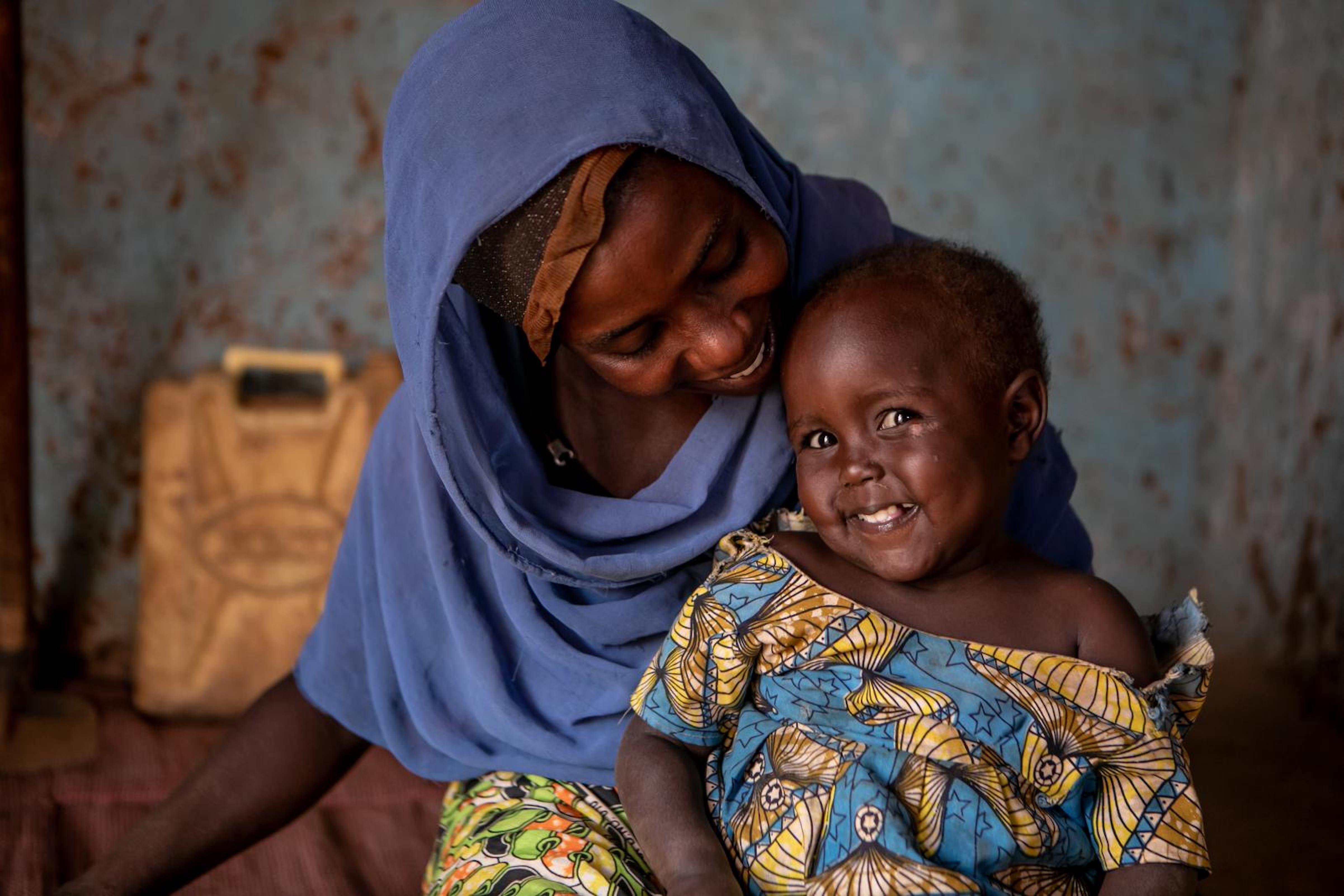 Kabiite Ajara (32anni) aiuta Nuriet (2anni 8mesi) a prendere la sua medicina contro l'HIV. Nuriet e Kabiite hanno entrambe l'HIV e hanno bisogno dei medicinali giornalmente.