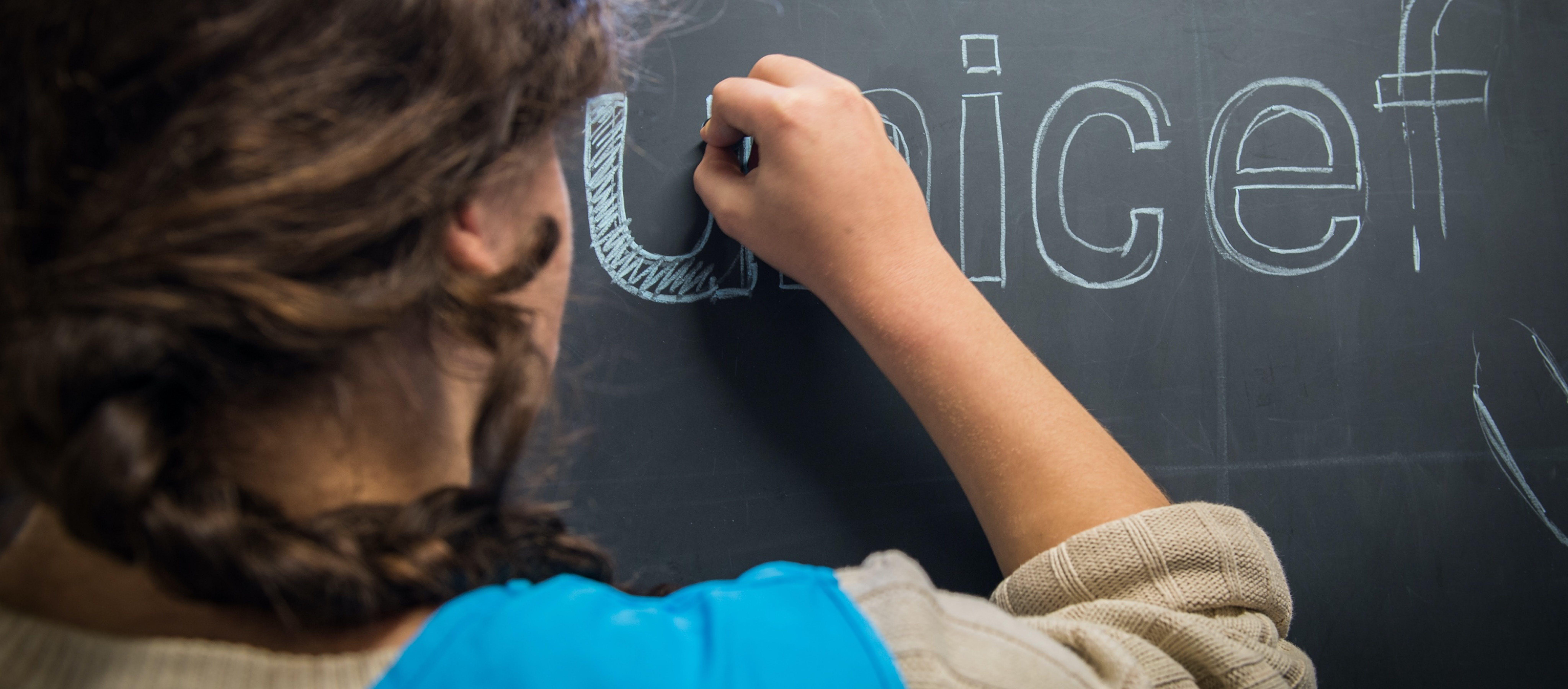 Volontaria disegna alla lavagna il logo UNICEF