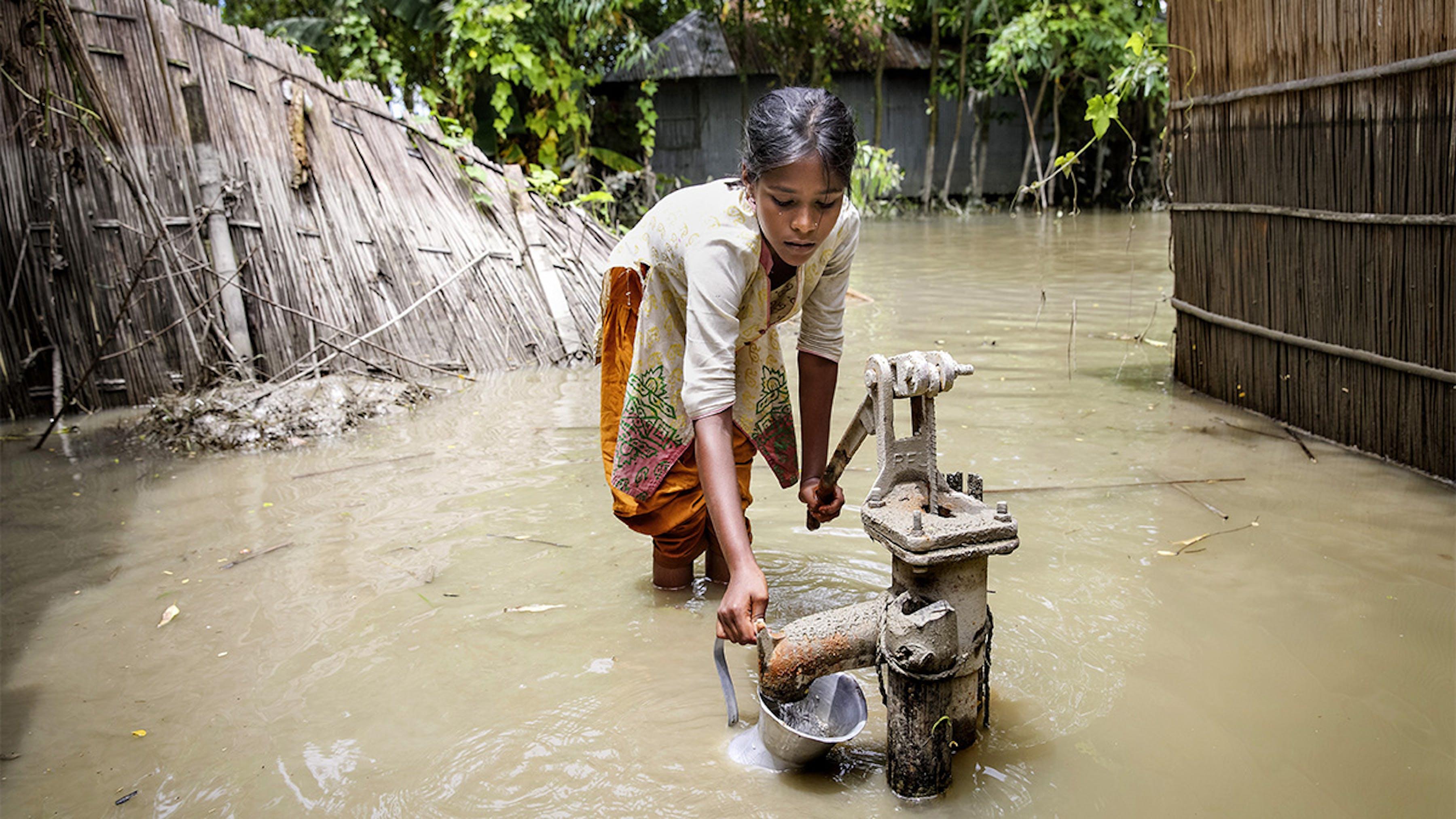 Bangladesh, durante un'inondazione una ragazza cerca di prendere acqua pulita da una pompa.