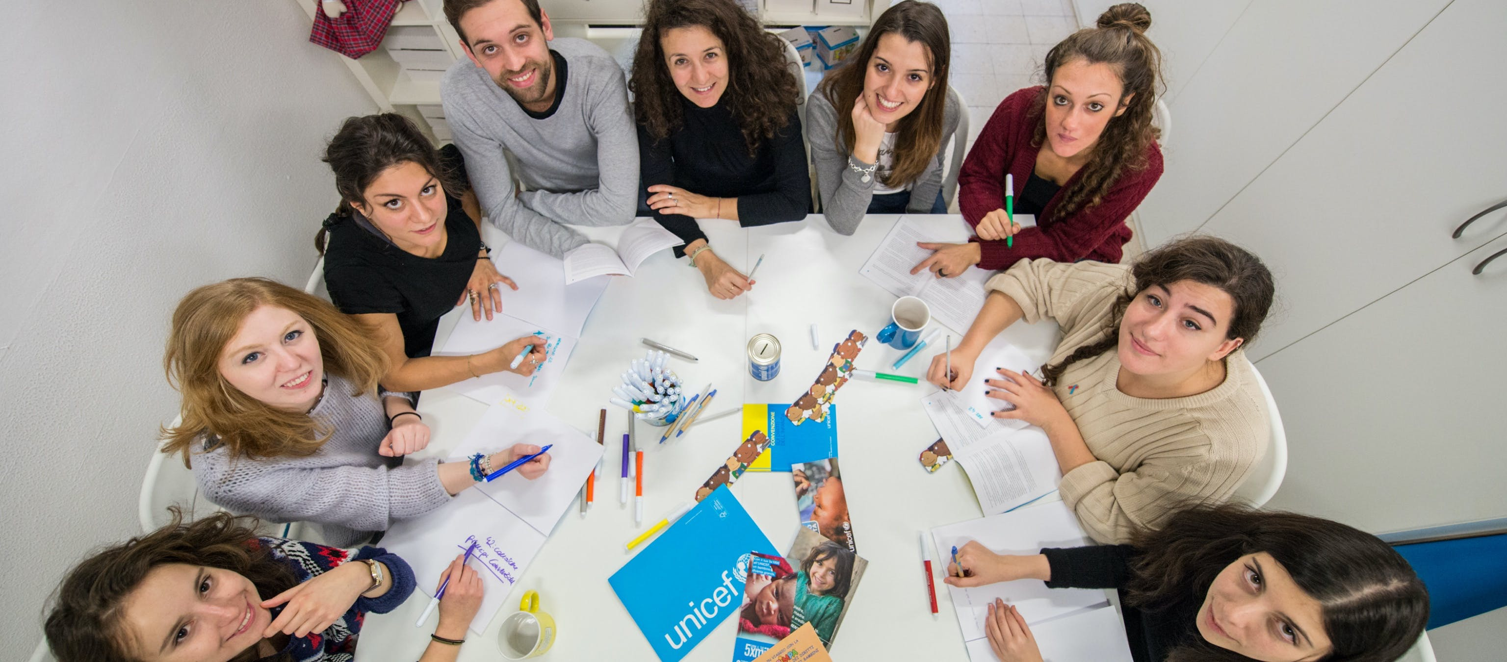 Volontari YOUNICEF attorno a un tavolo durante delle attività