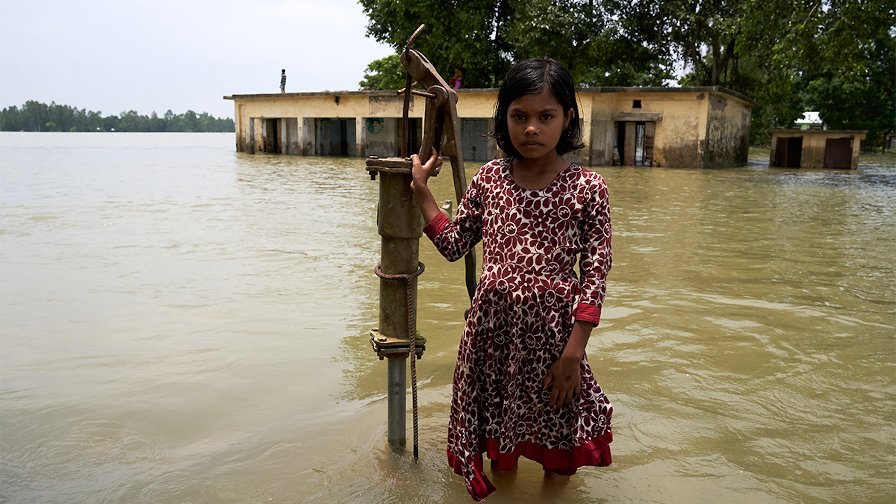 Bangladesh, una bambina di fronte alla sua scuola parzialmente sommersa dalle acque.