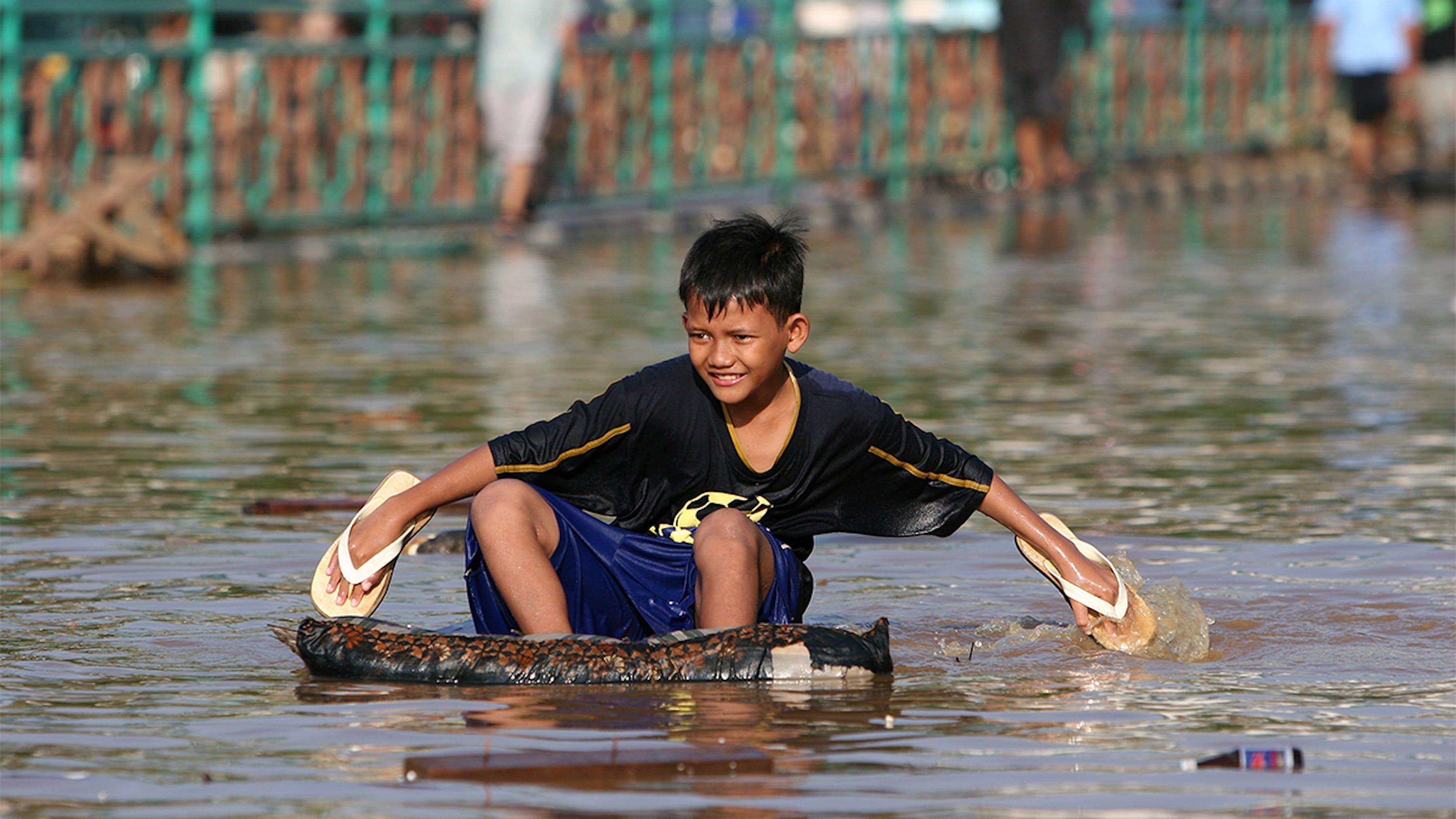 Indonesia, un ragazzo su un galleggiante improvvisato  usa le sue scarpe per remare.
