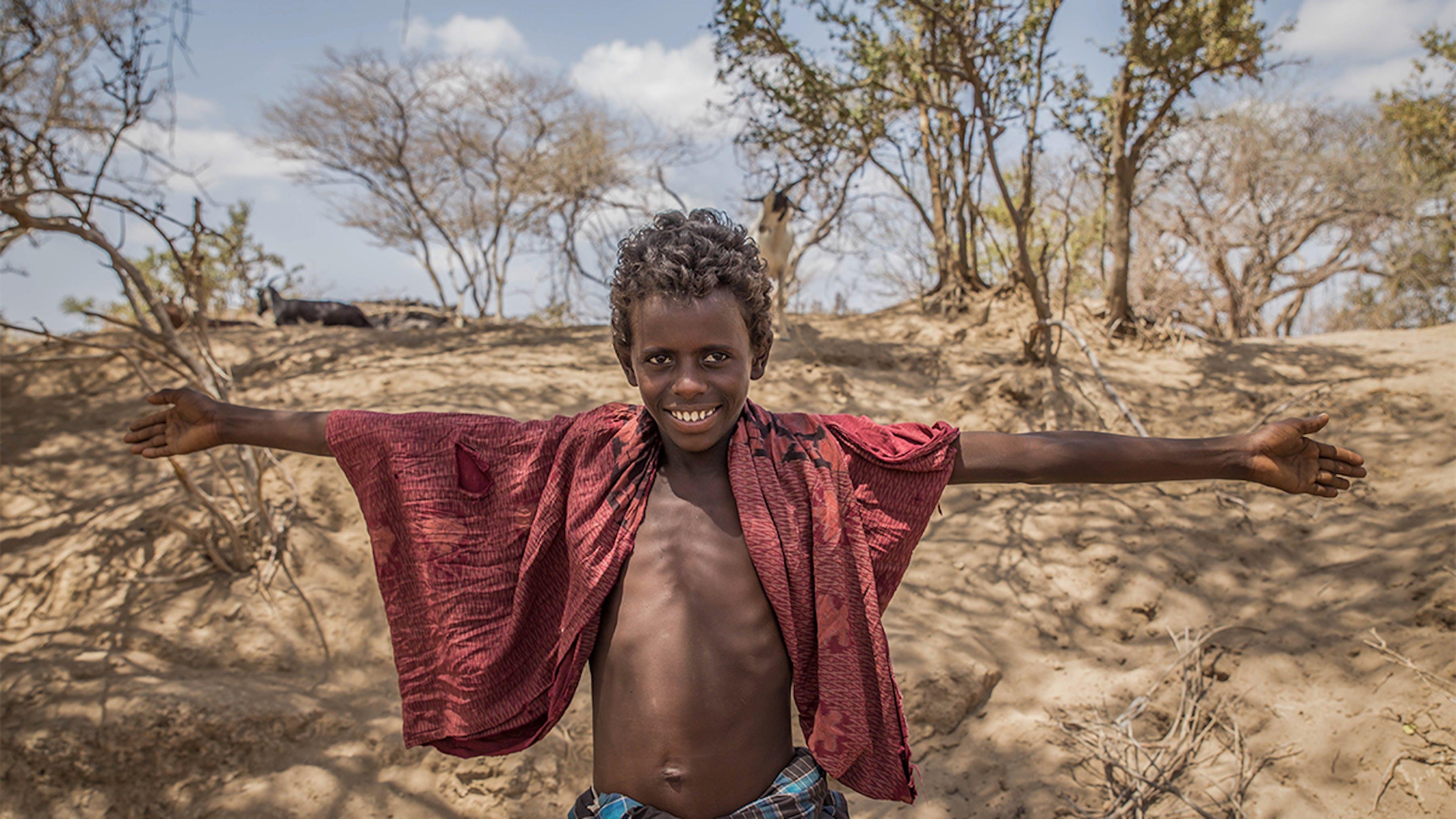 Etiopia, un bambino posa davanti al terreno della sua famiglia arido a causa della siccità.