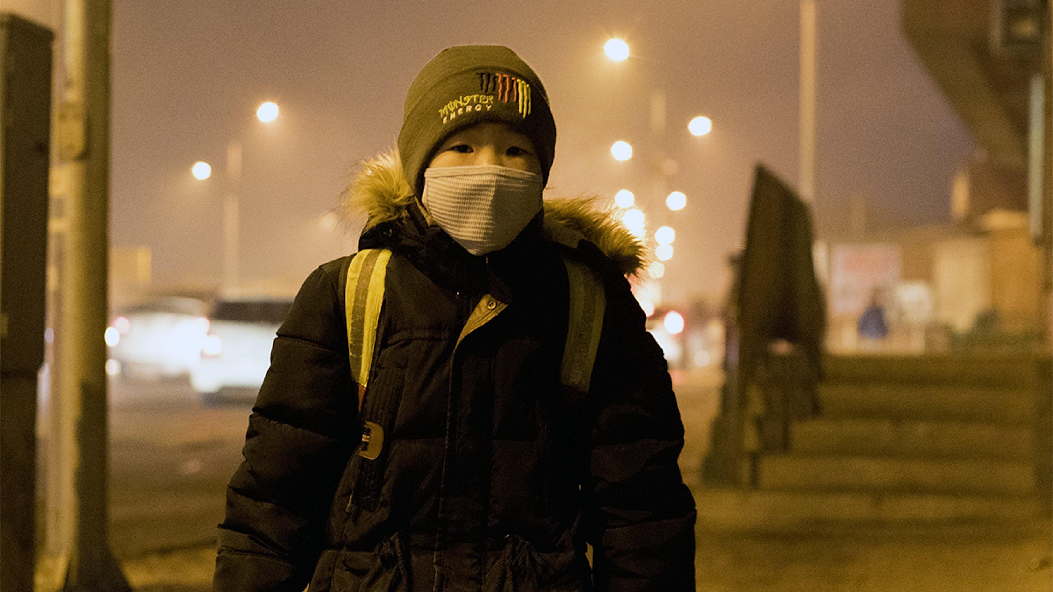 Mongolia, un ragazzo con una mascherina si protegge dall'inquinamento atmosferico molto elevato.