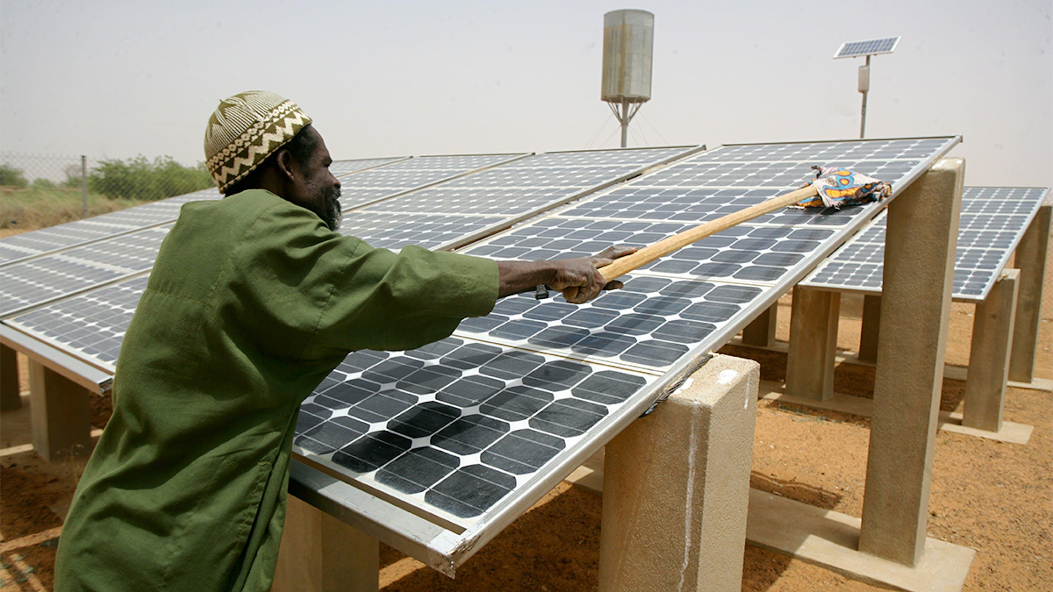 Mali, un uomo pulisce i pannelli solari nel villaggio di Konza Pheul.