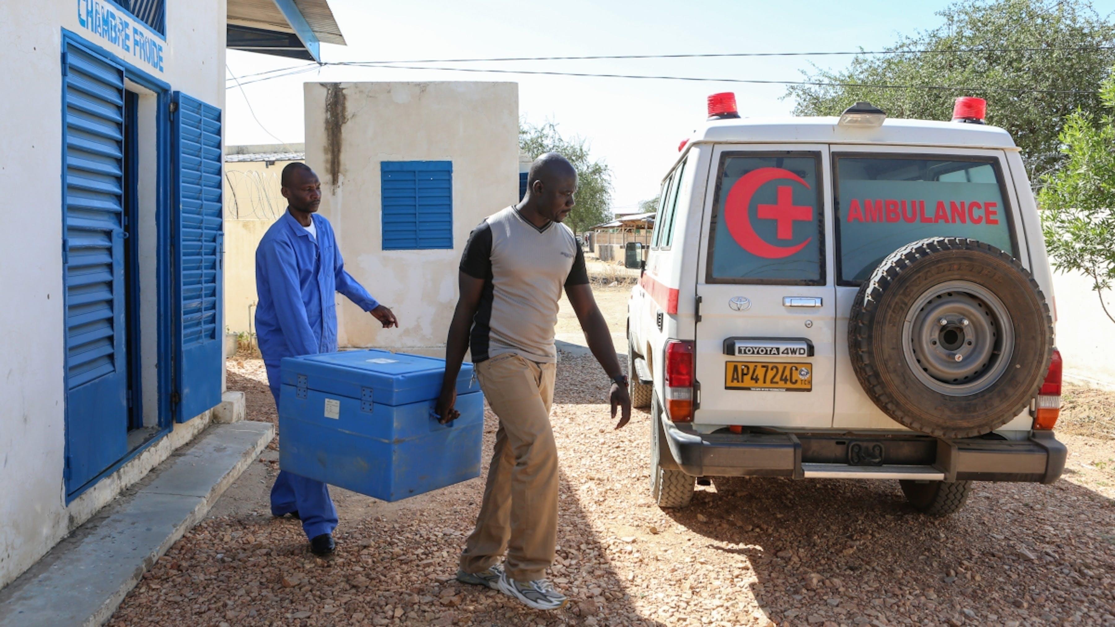 Ciad, due operatori trasportano un contenitore frigo di vaccini a un'ambulanza della Croce Rossa