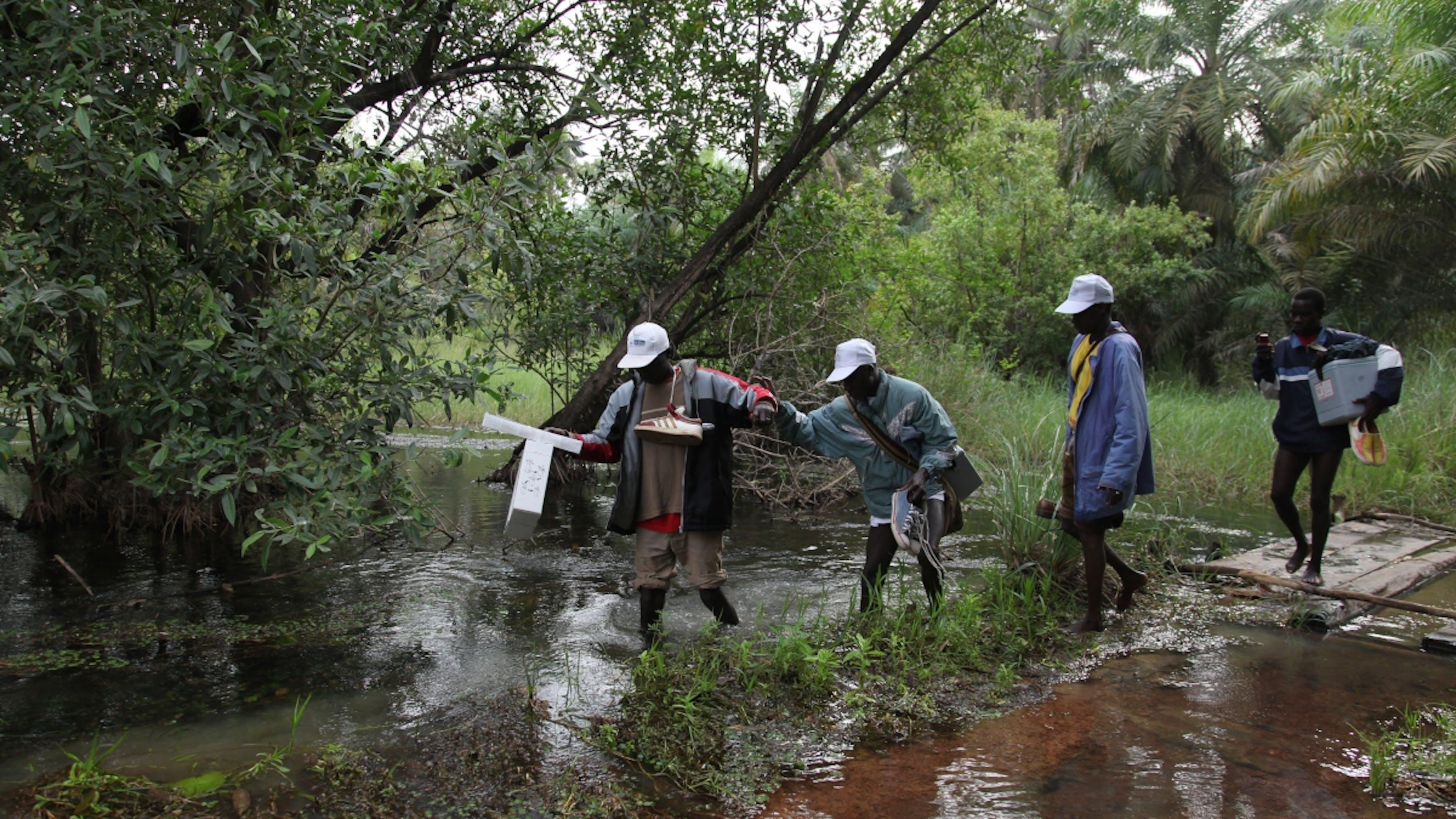 Guinea Bissau, un team di vaccinatori trasporta un carico di vaccini attraverso una palude