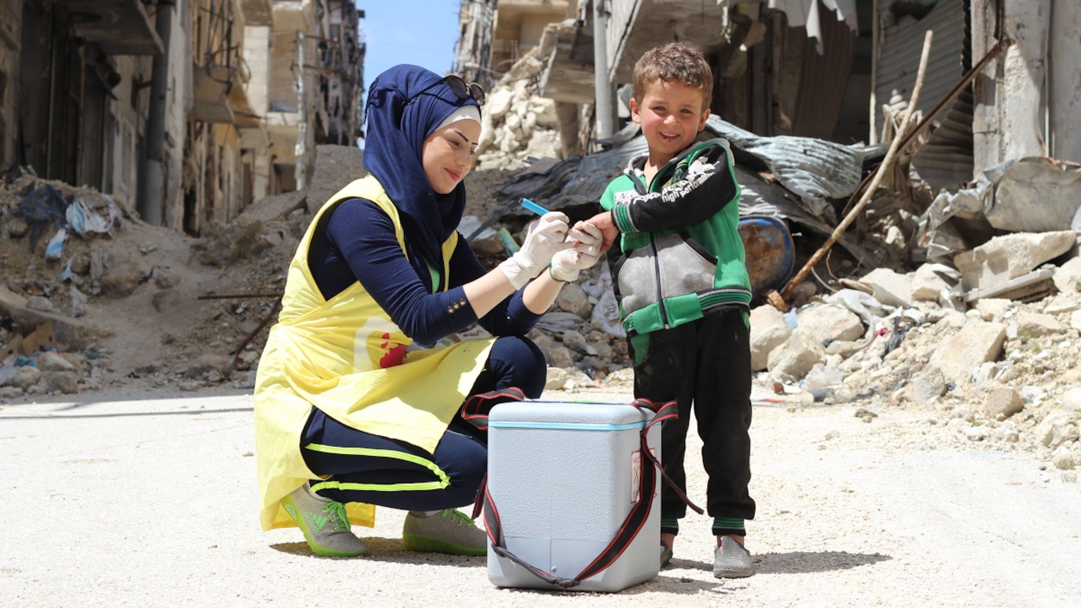 Siria, un operatrice sanitaria vaccina Yousef, di 5 anni nel quartiere di Hulluk ad Aleppo