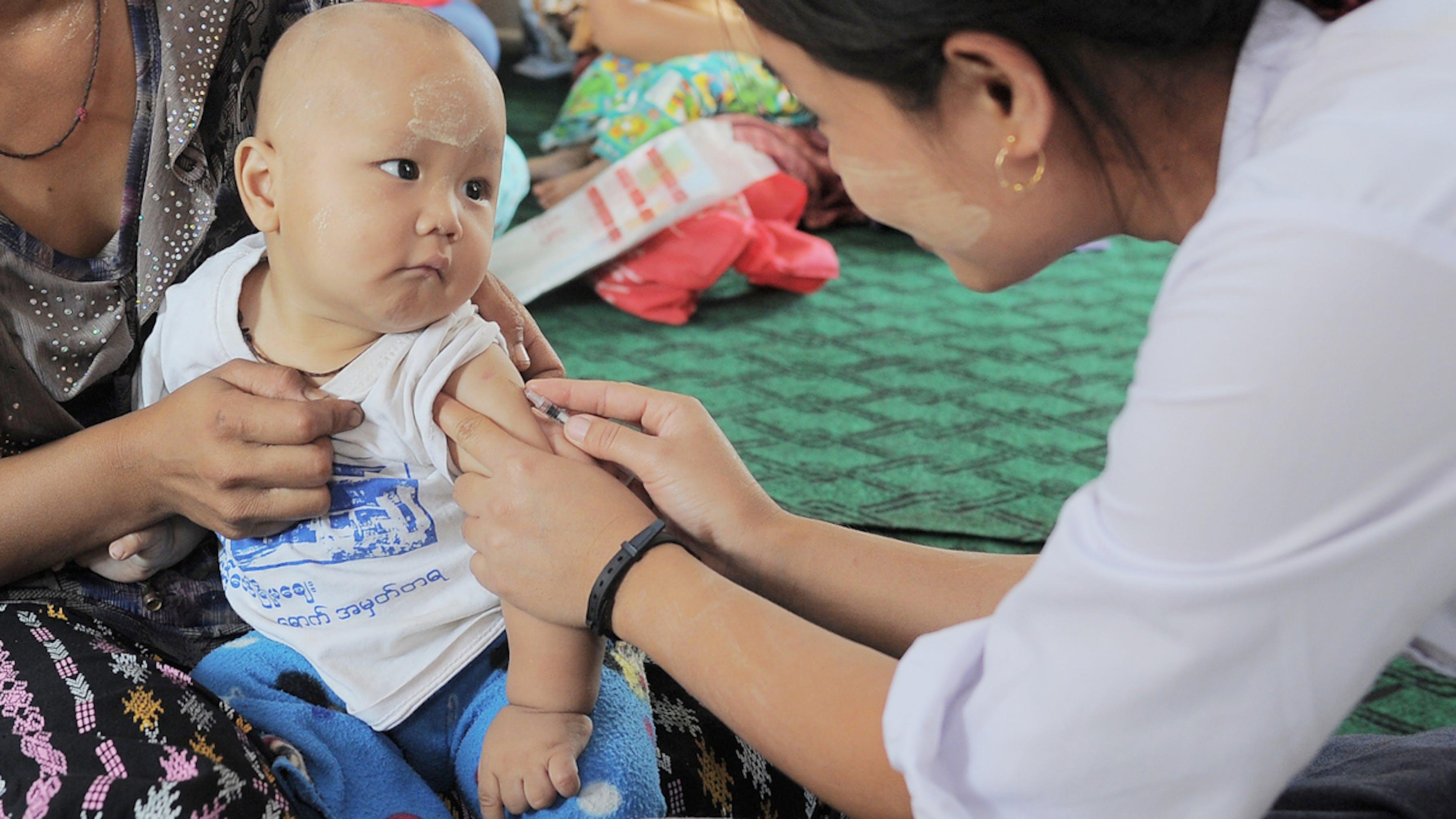 Myanmar, un bambino guarda l'ostetrica mentre riceve il vaccino contro il morbillo