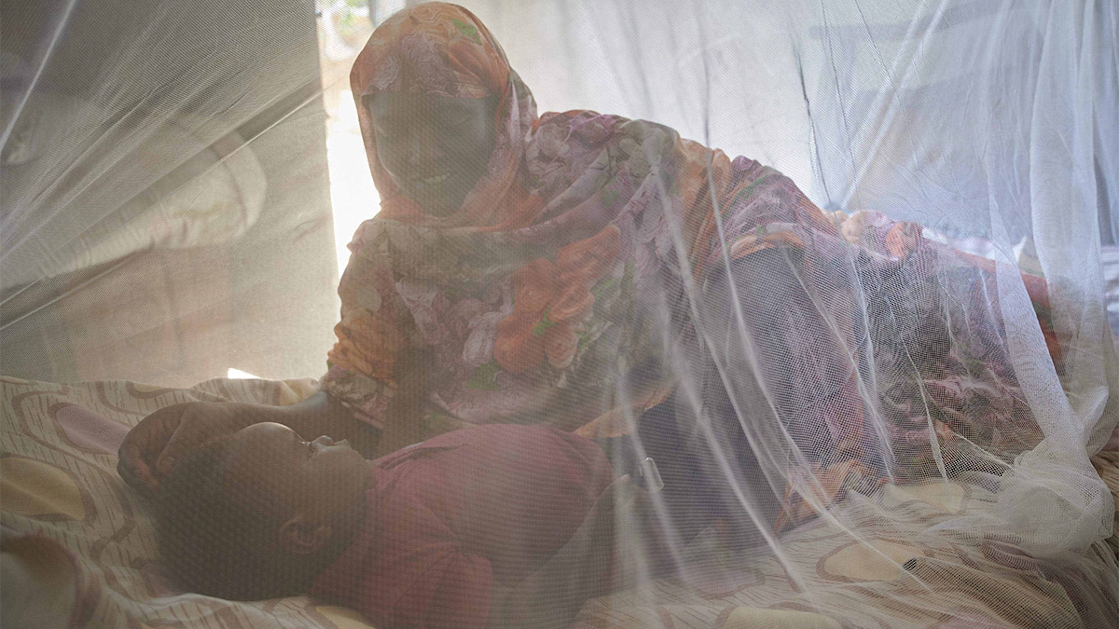 Sudan, una mamma guarda la sua bambina dormire sotto una zanzariera