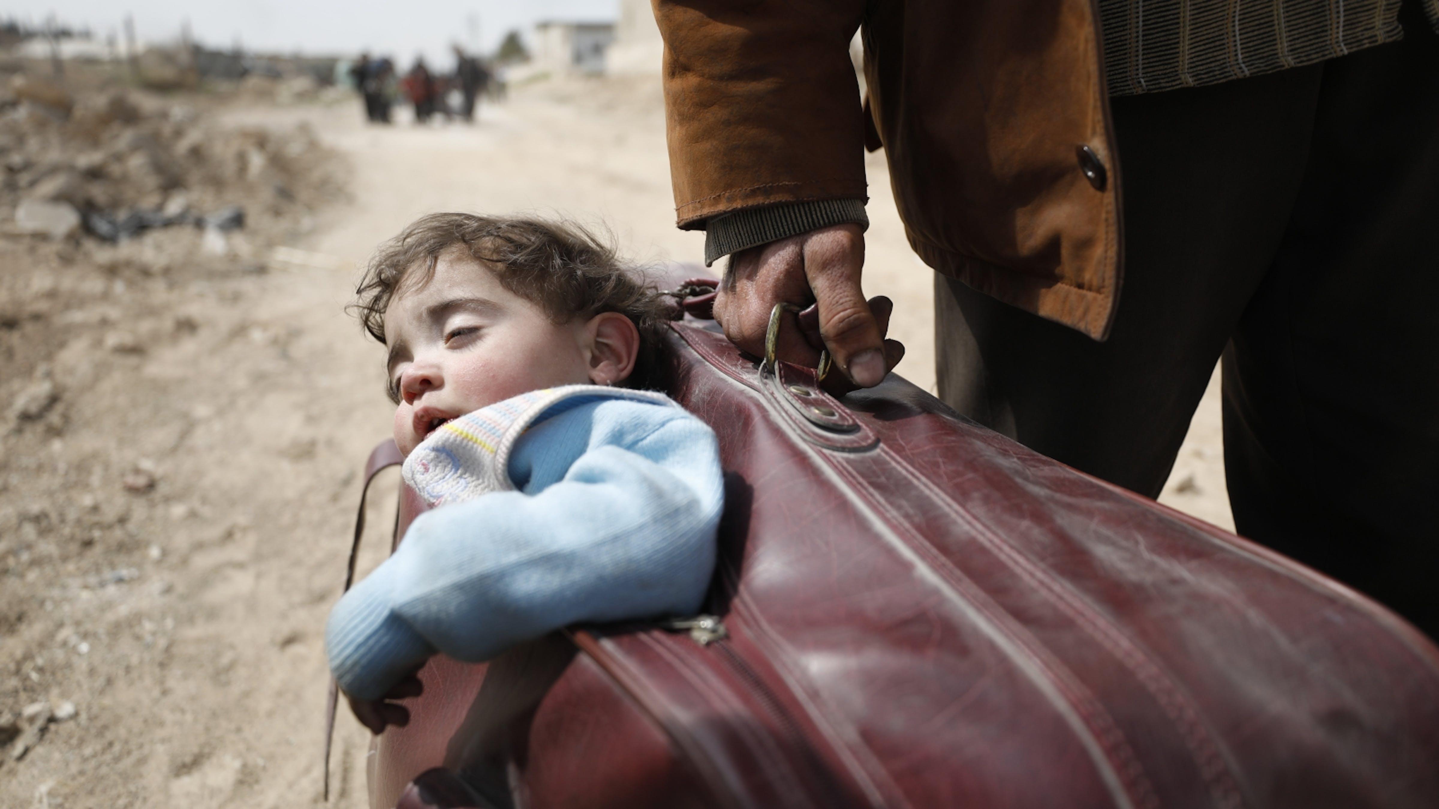 Siria, bambino nella valigia che affronta il viaggio per allontanarsi dalla guerra.