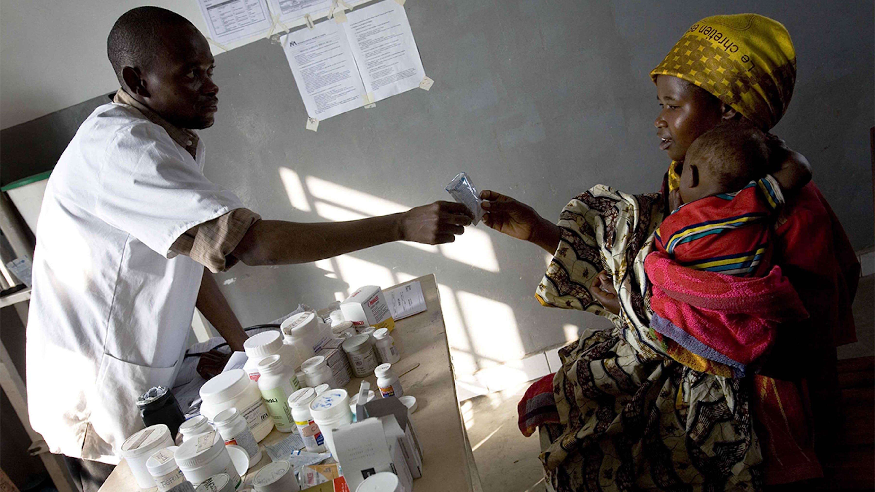 Congo, un infermiere distribuisce farmaci a una donna con il bambino