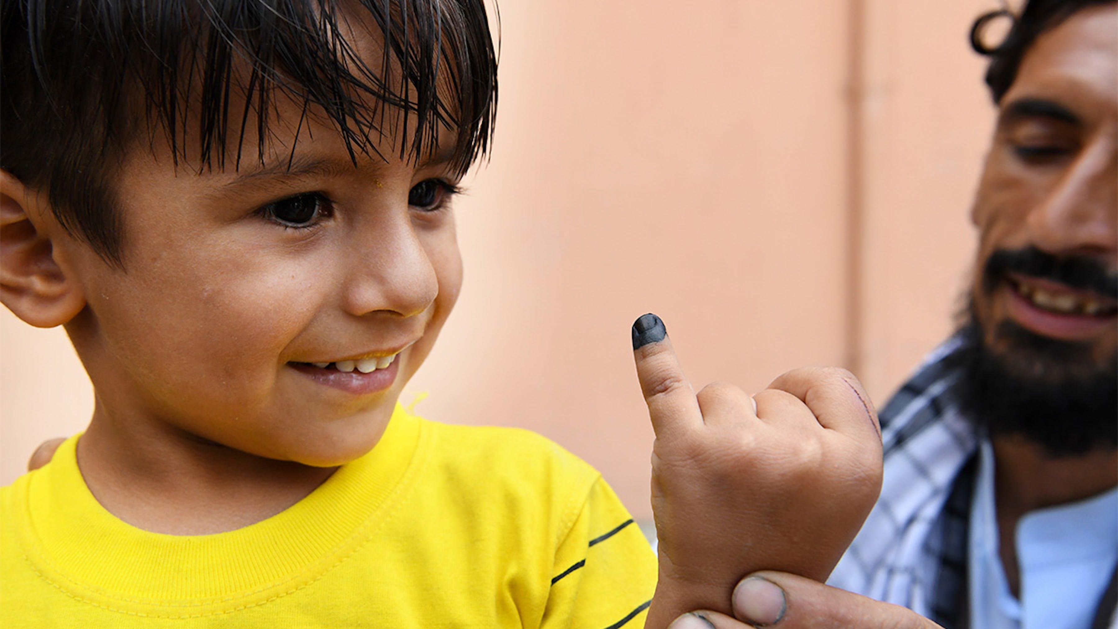 Afghanistan, un bambino mostra il dito segnato, è stato appena vaccinato contro la polio