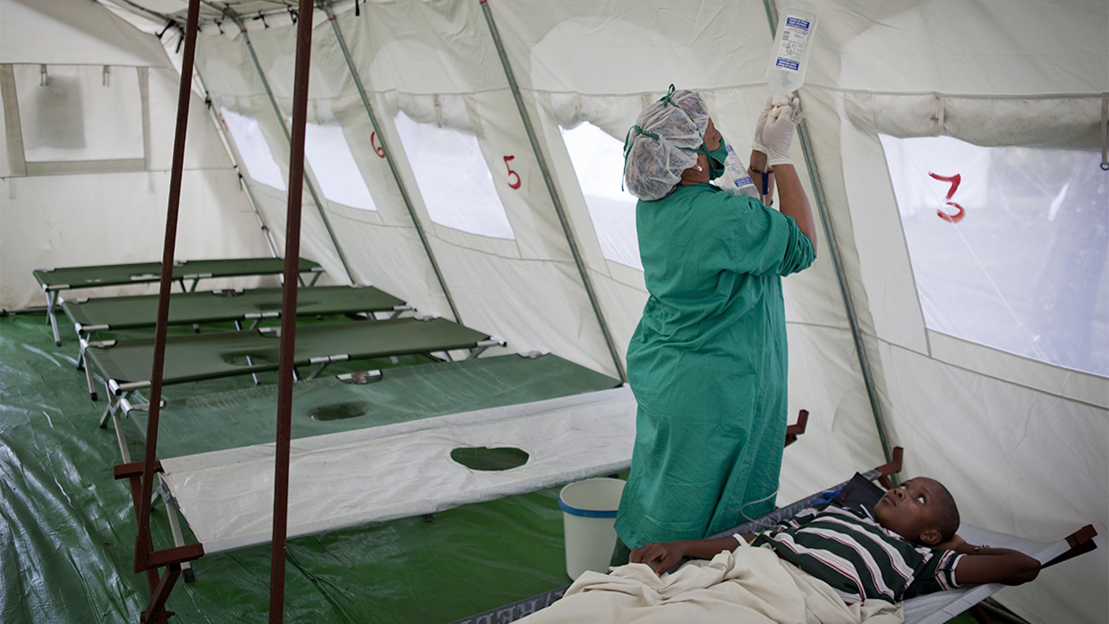 Haiti, una dottoressa sostituisce un sacchetto di liquidi per via endovenosa ad un ragazzo affetto da colera