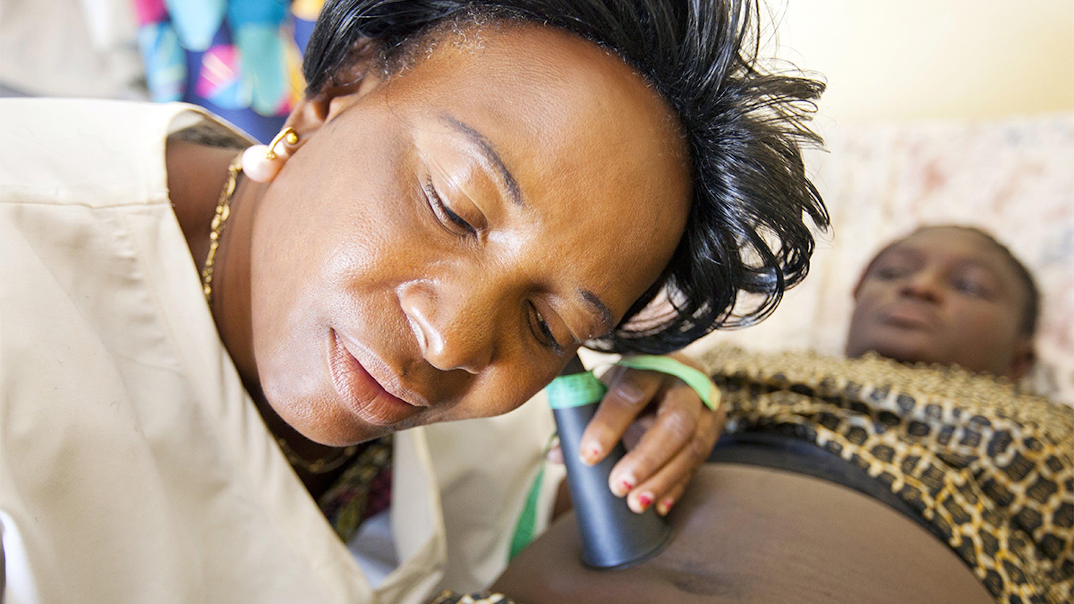 Congo, un'infermiera visita una donna incinta.