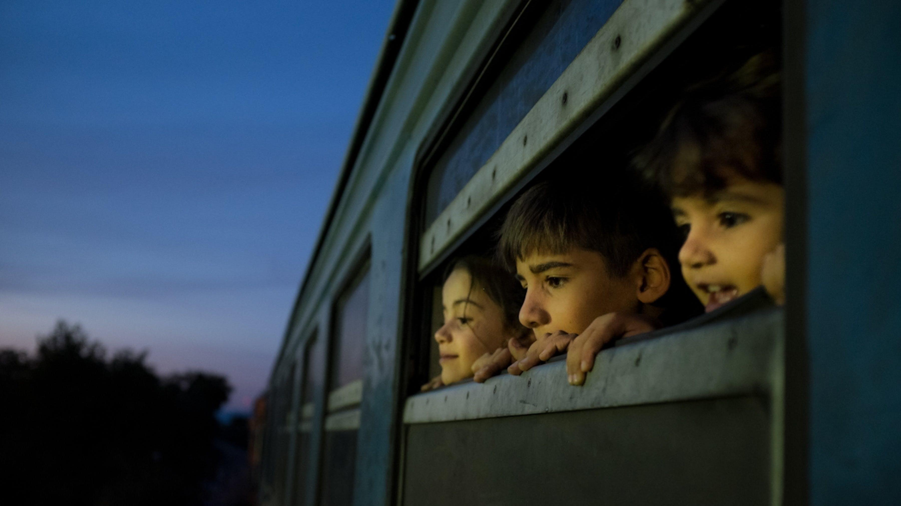 Macedonia, tre bambini rifugiati affacciati al finestrino di un treno.