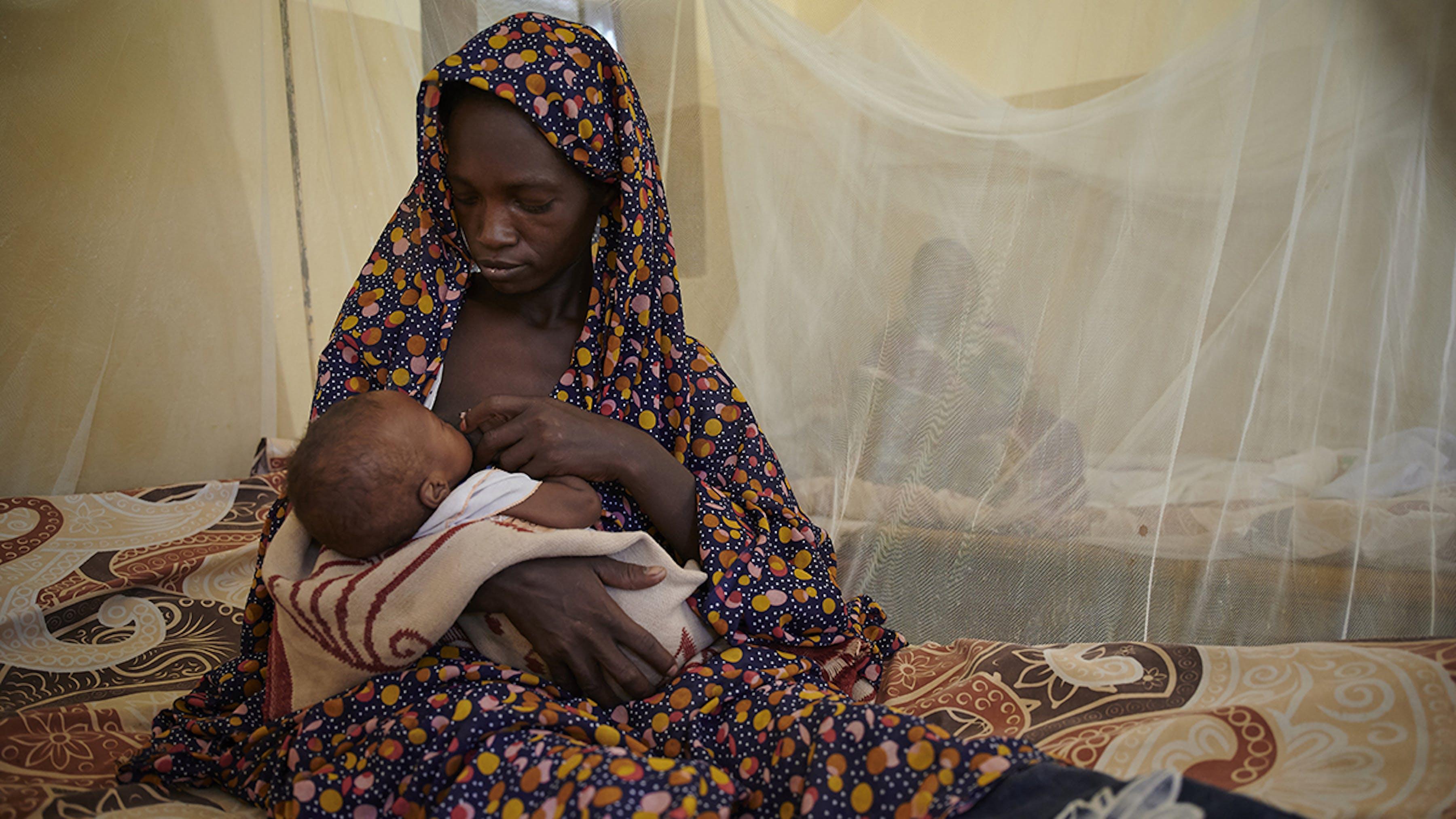 Sudan, seduta su un letto, sotto una zanzariera, una mamma allatta suo figlio al seno