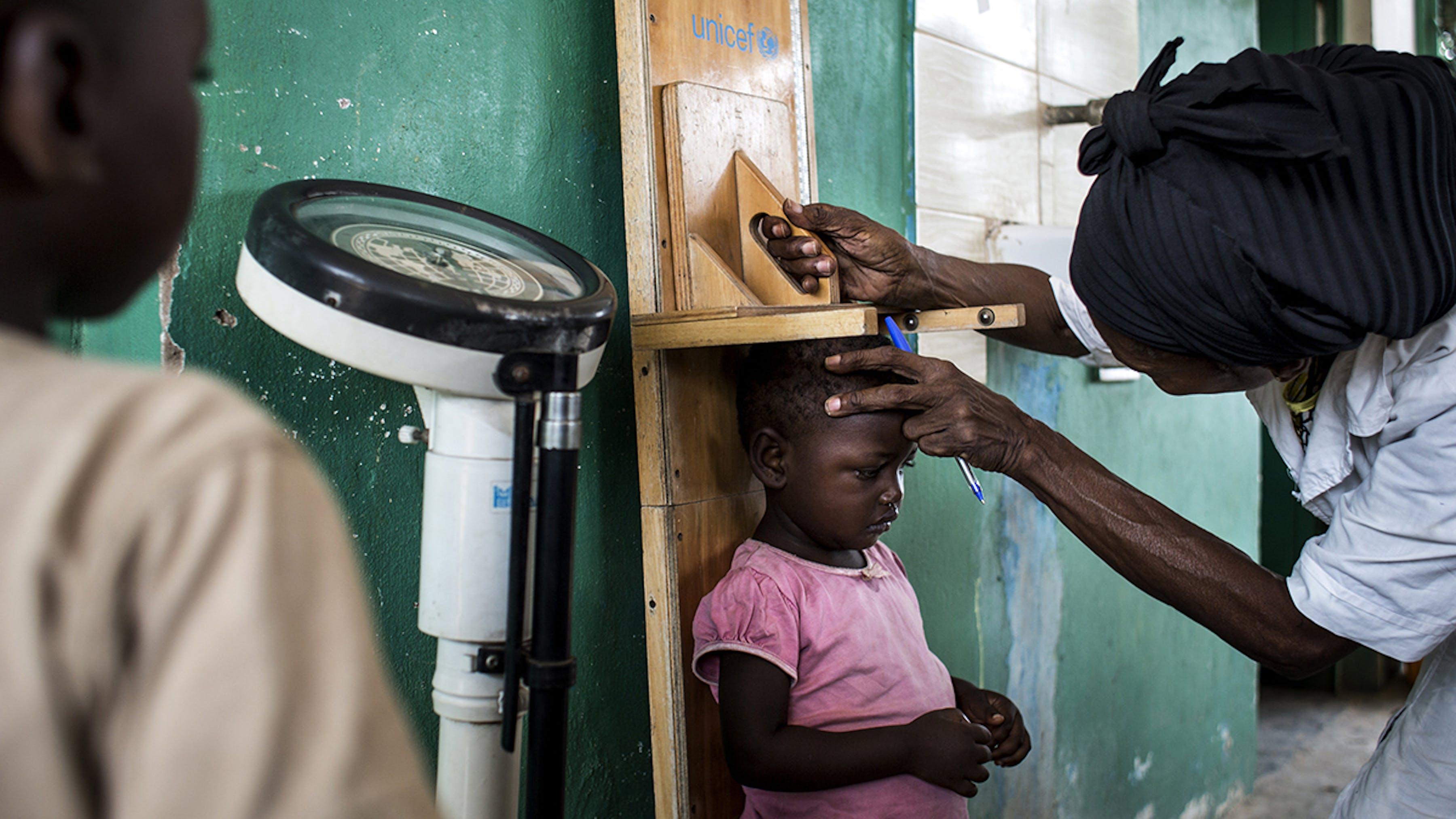 Congo, in una clinica pediatrica un'operatrice sanitaria misura l'altezza ad una bambina