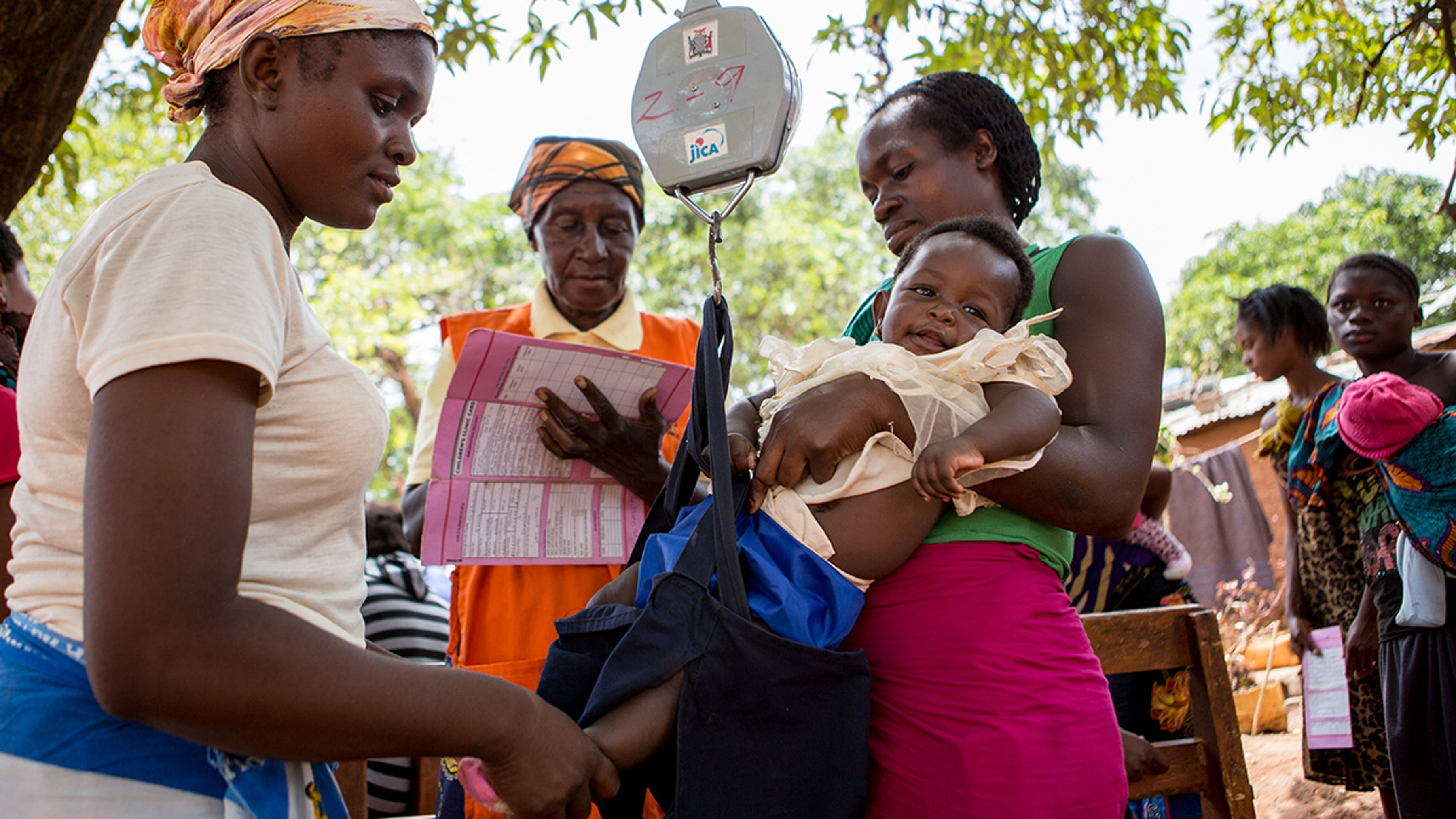 Zambia, un bambino viene pesato da un'operatrice comunitaria mentre la collega prende appunti sul peso
