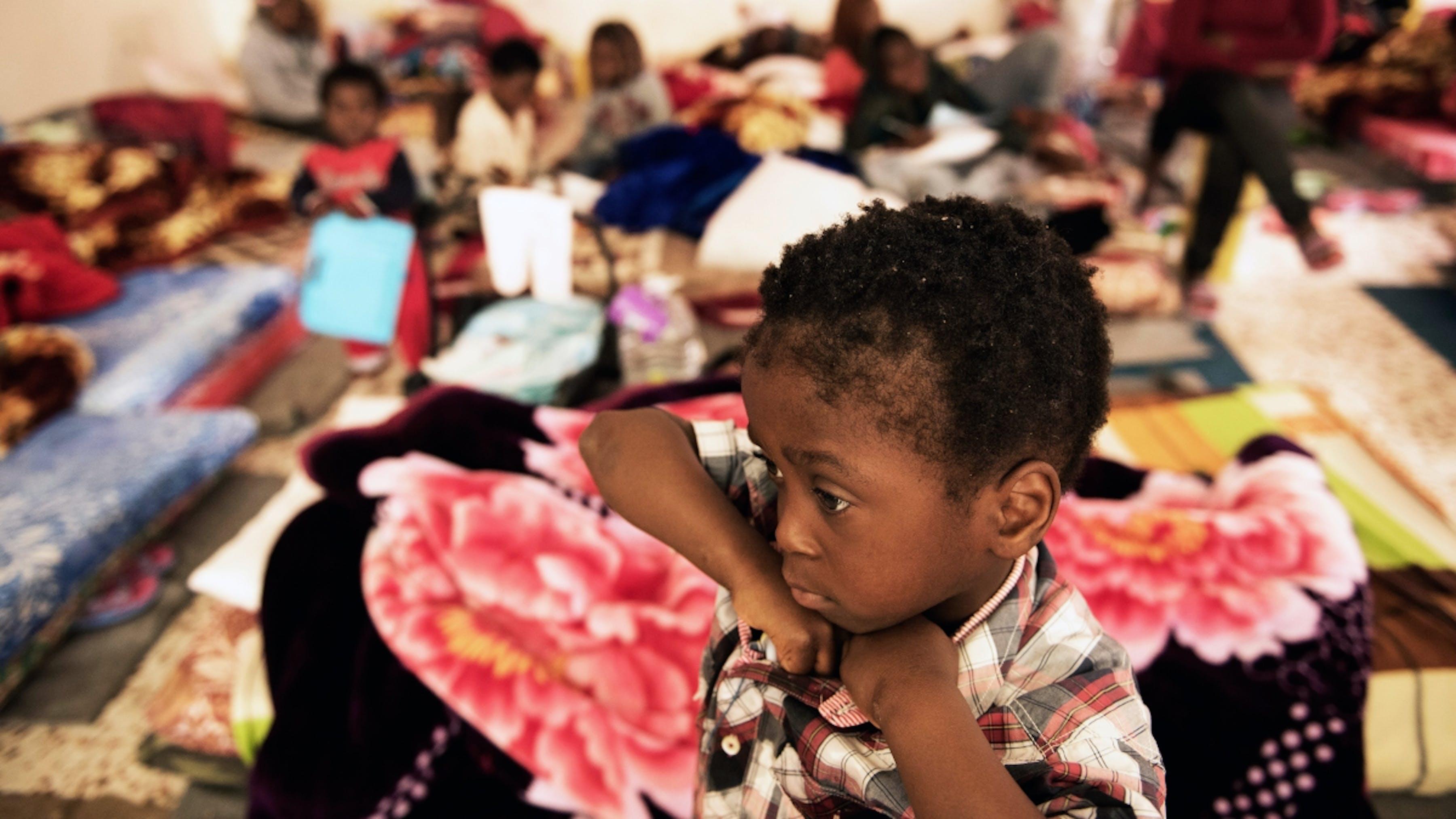 Libia, un bambino rifugiato seduto sul pavimento di un centro di detenzione.