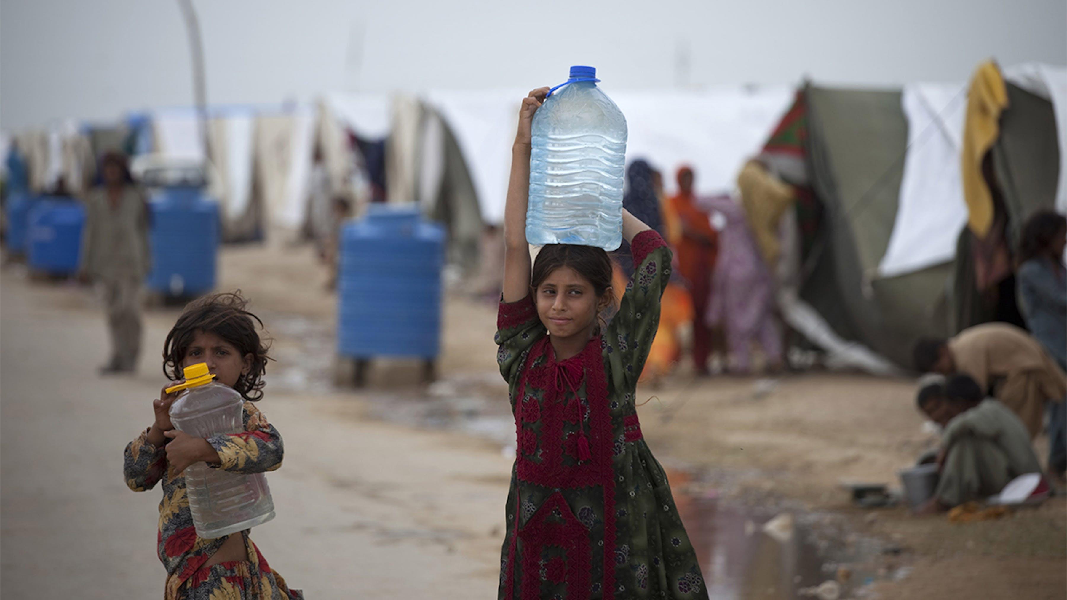 Pakistan, due ragazze portano grandi bottiglie d'acqua in un campo per le persone sfollate a inondazioni