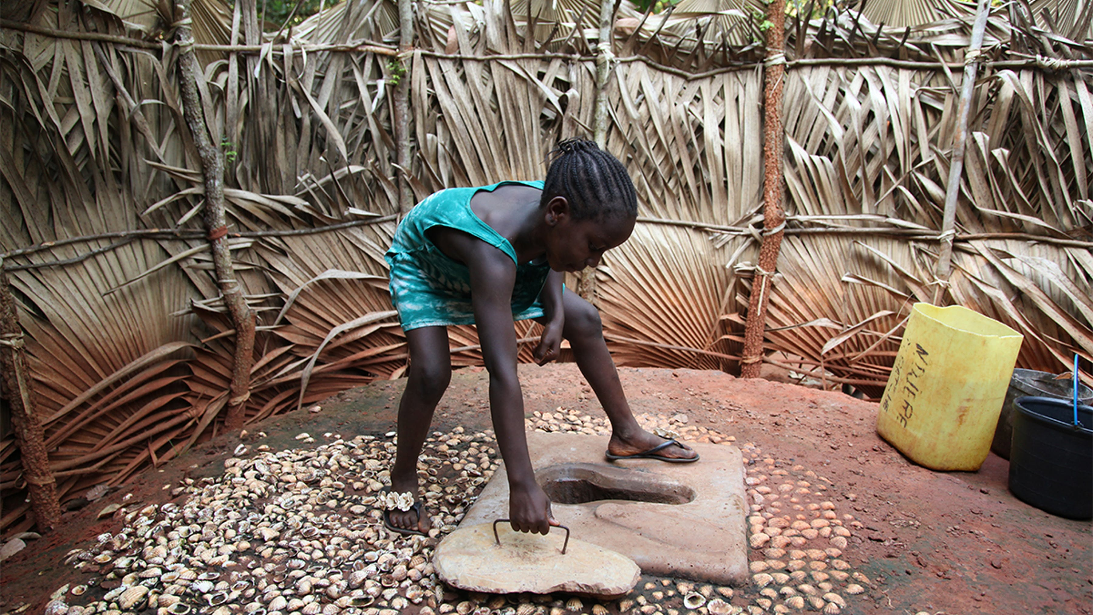 Guinea Bissau, una ragazza chiude una latrina a fossa