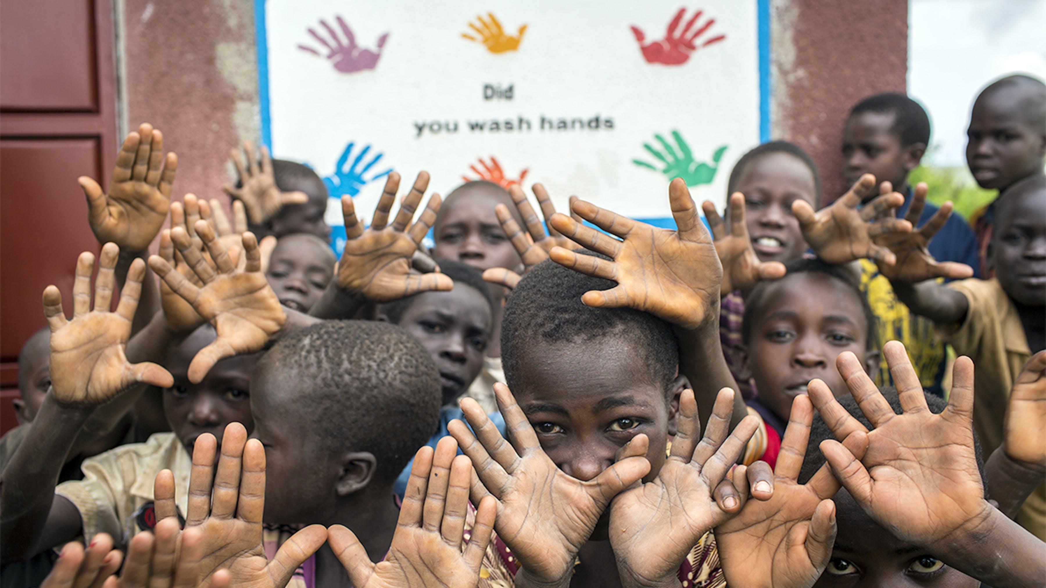Uganda, studenti di fronte a un cartello che promuove il lavaggio delle mani a scuola