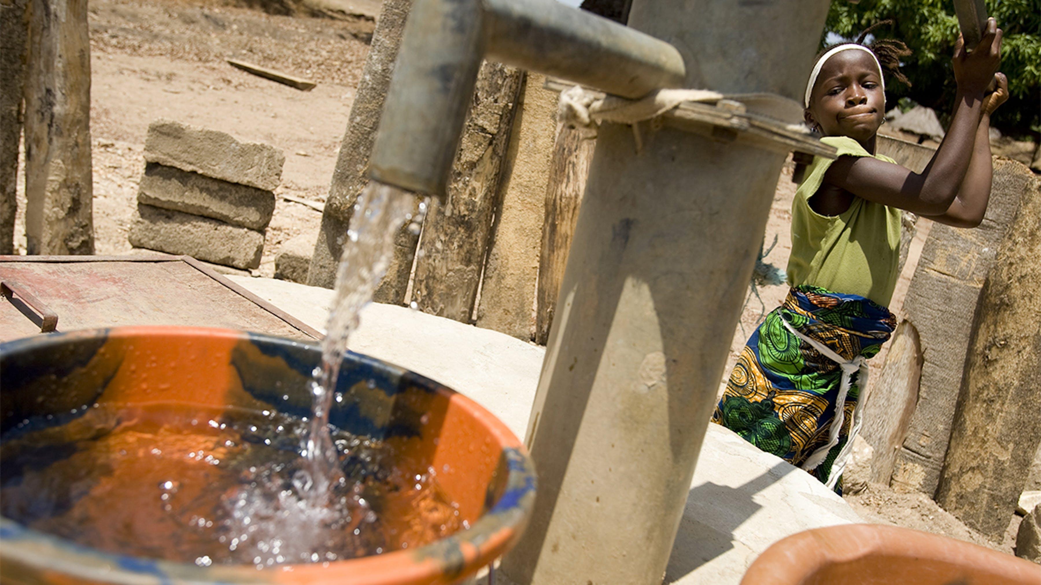 Sierra Leone, una ragazza raccoglie l'acqua presso la pompa a mano della comunità locale
