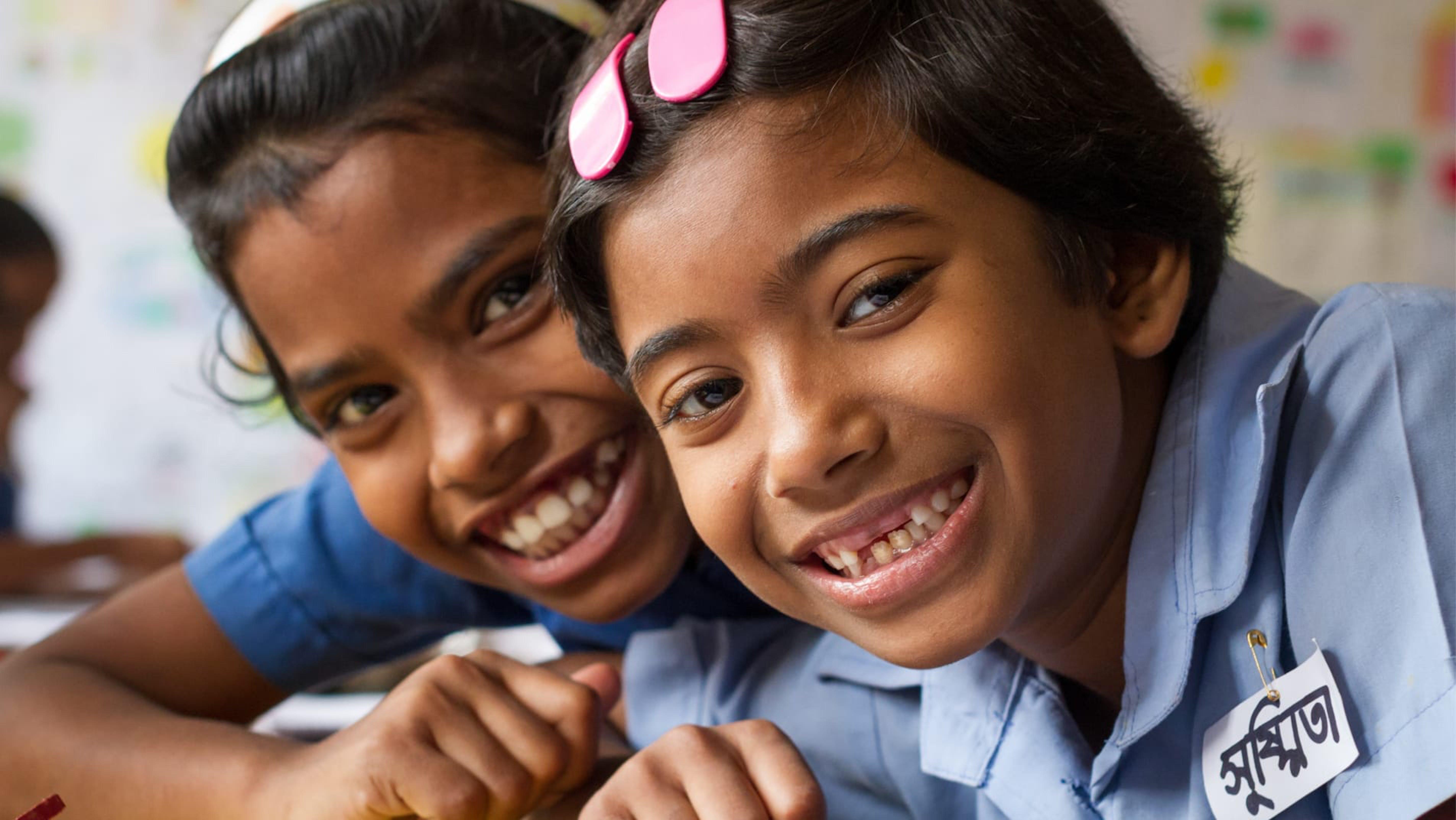 Shushmita e la sua amica Binky sorridono mentre sono a scuola, in Bangladesh.