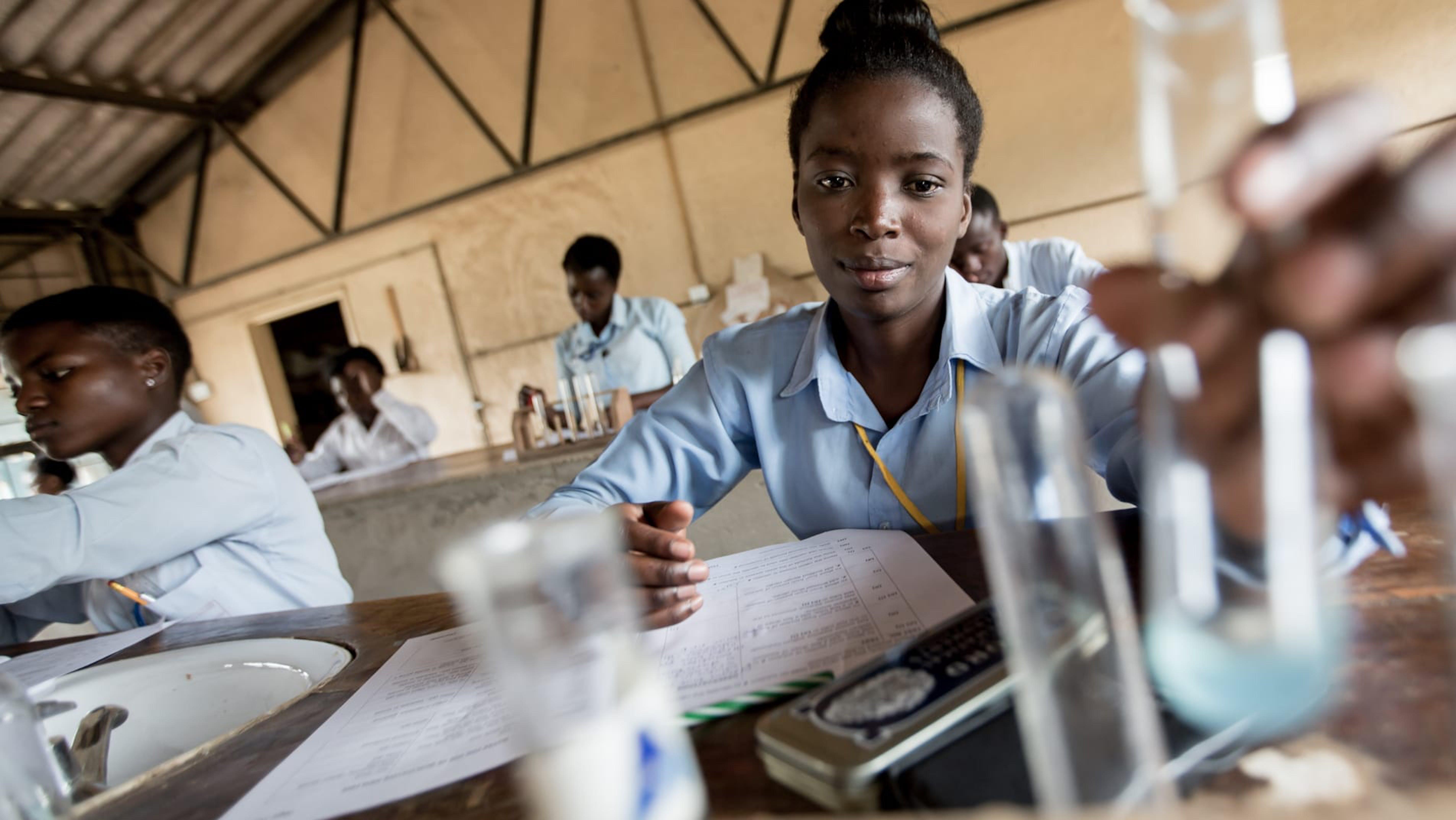 Zambia,una ragazza adolescente conduce un esperimento durante una lezione di chimica.