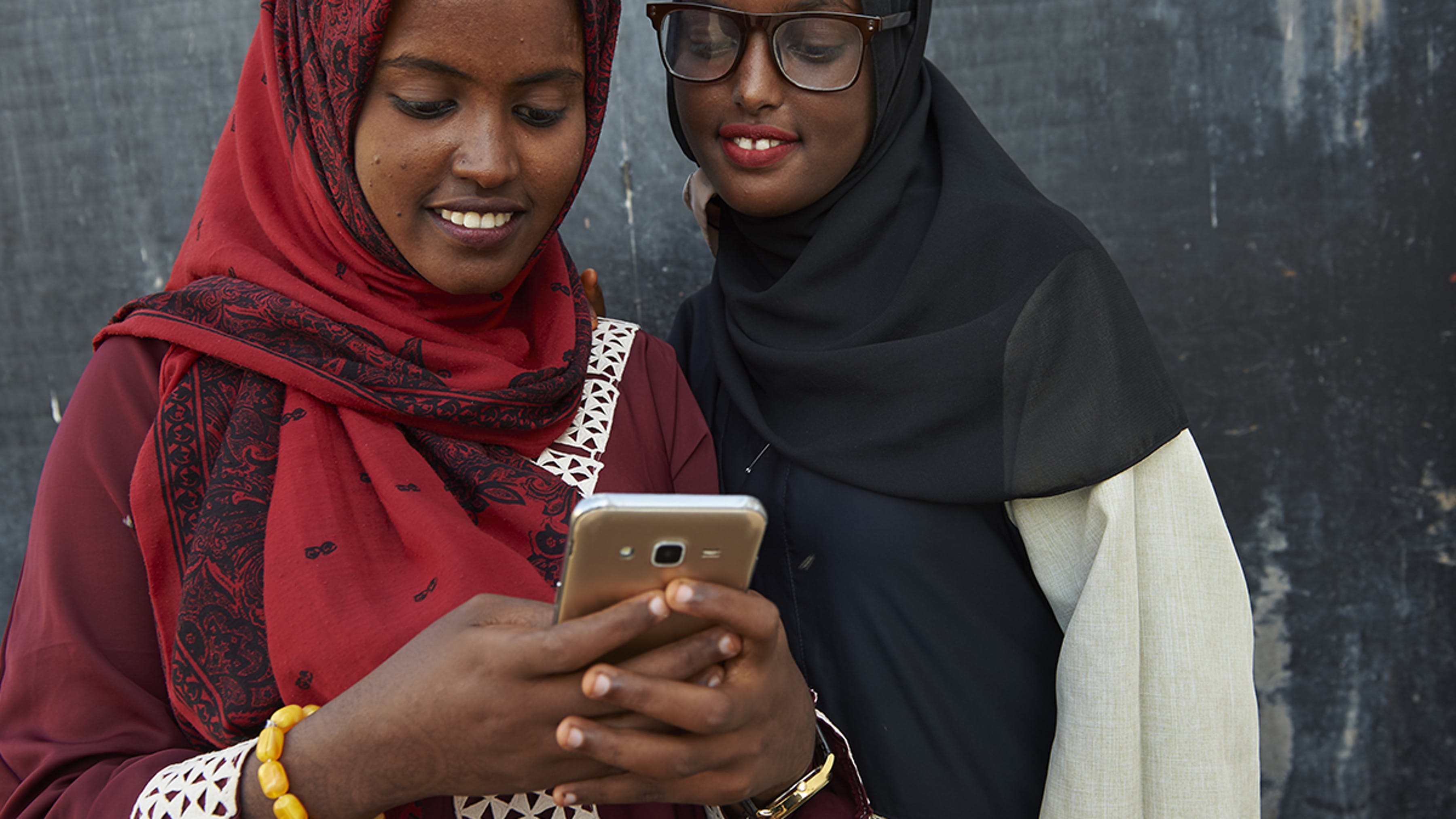 """Gibuti, due ragazze guardano i post sui social media mentre partecipano a un evento """"Lifeskills""""."""