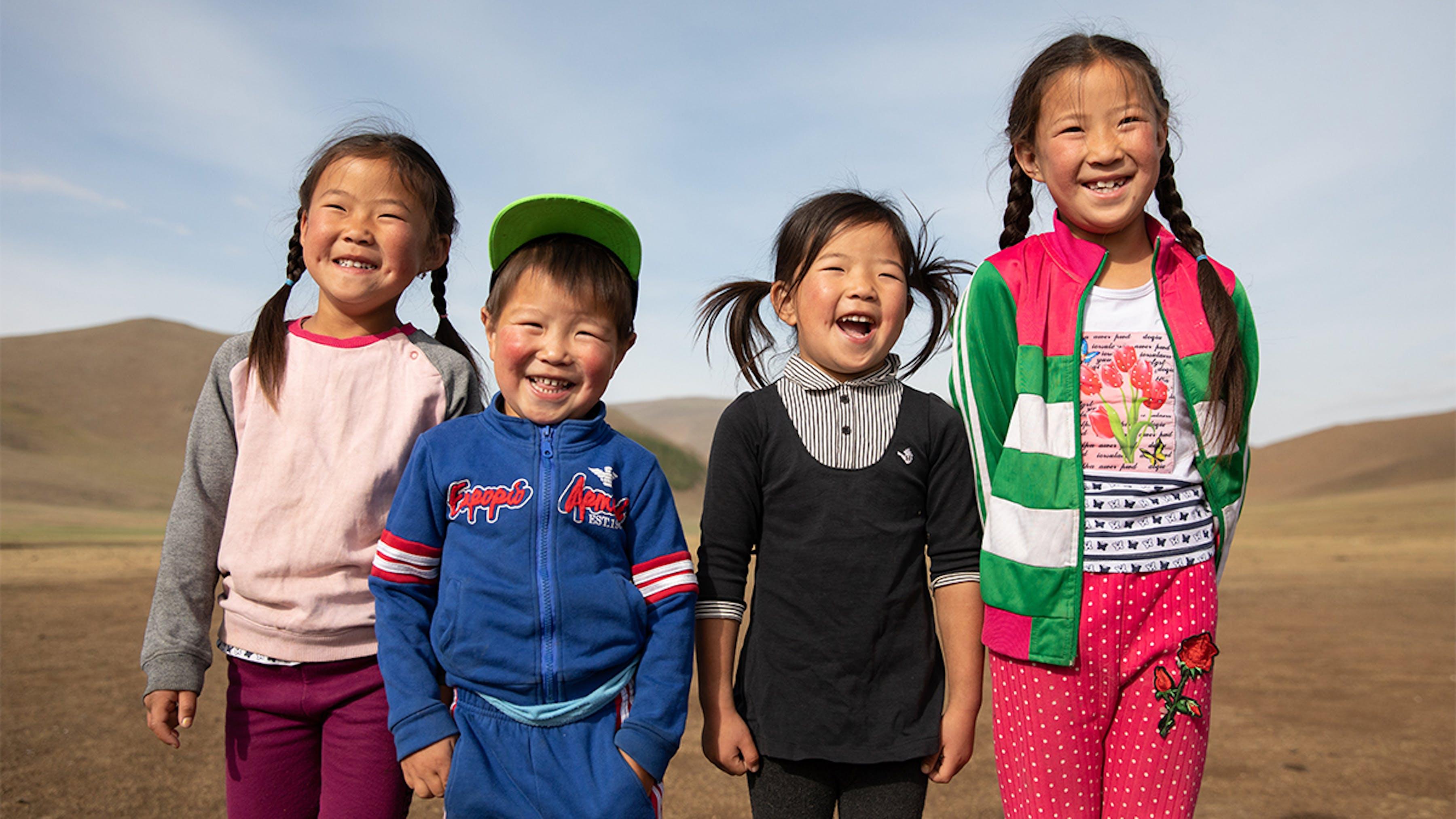 Mongolia, 4 bambini nomadi sorridono: nella zona in cui vivono l'accesso alle scuole è difficile.