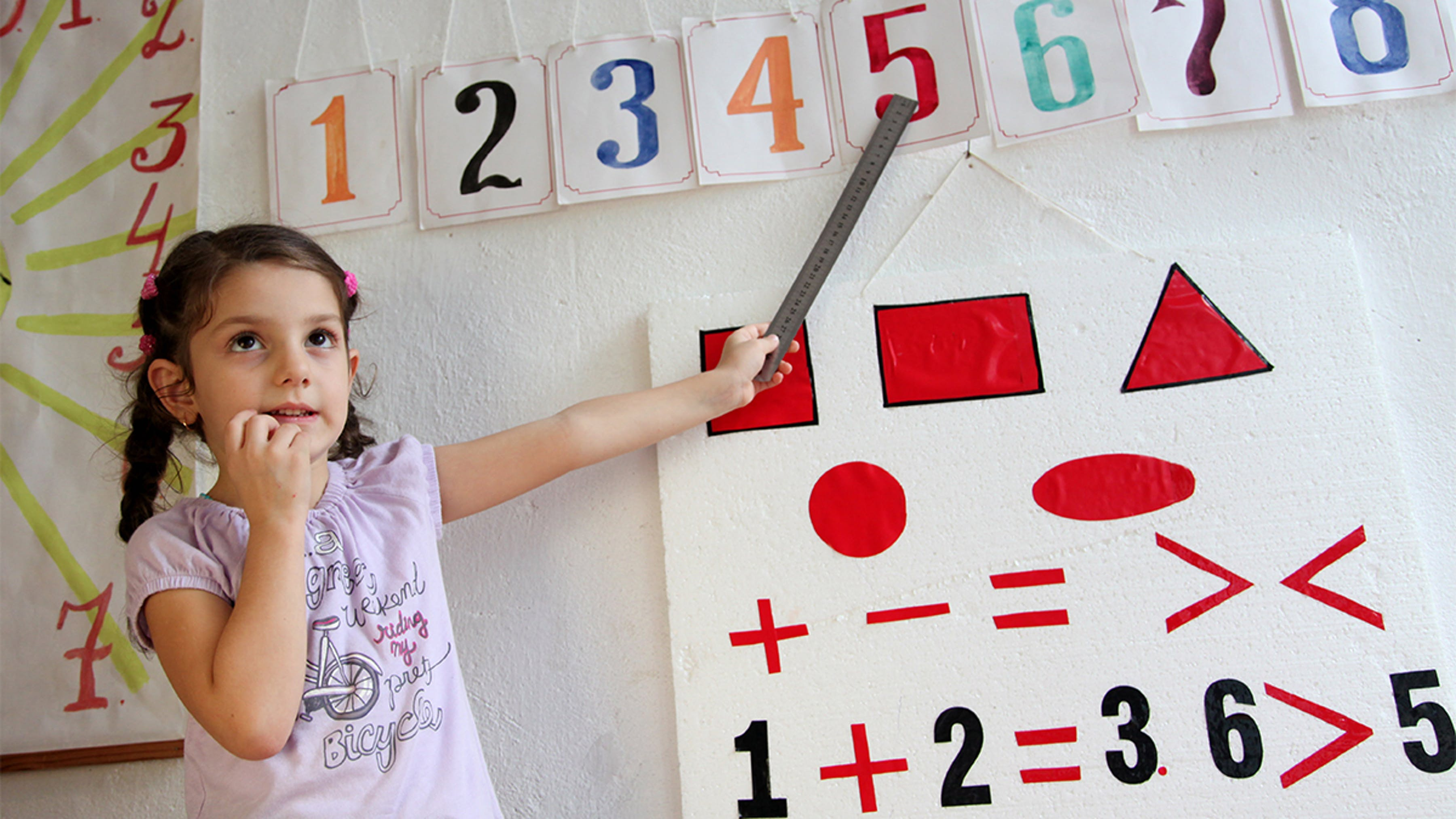 Azerbaijan, Una bambina impara a identificare i numeri nel suo primo giorno di scuola.