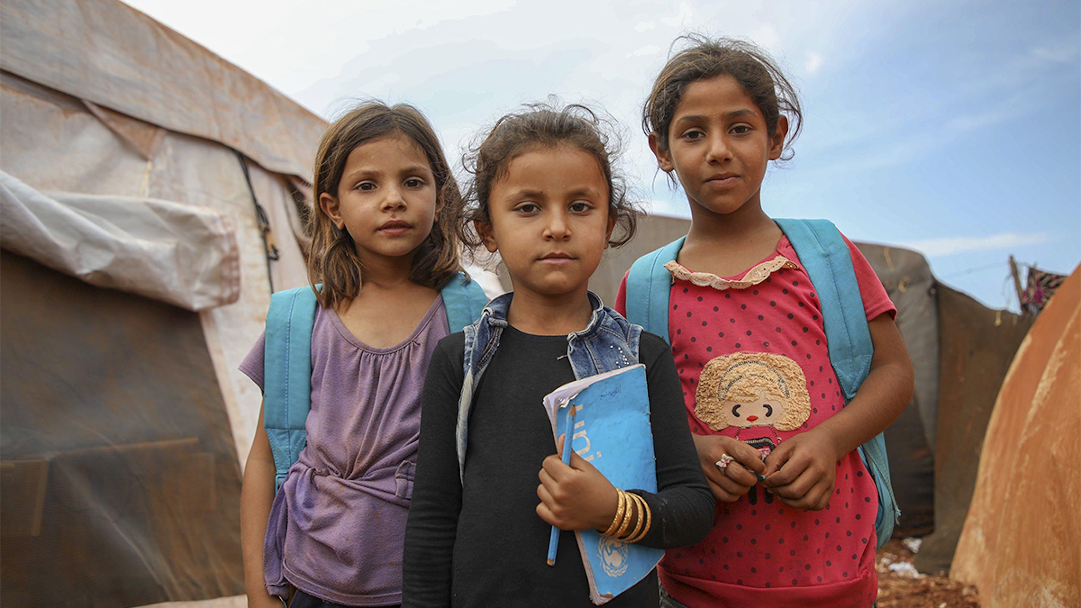 Siria, ragazze con zaini e quaderni UNICEF fuori da una tenda scuola.