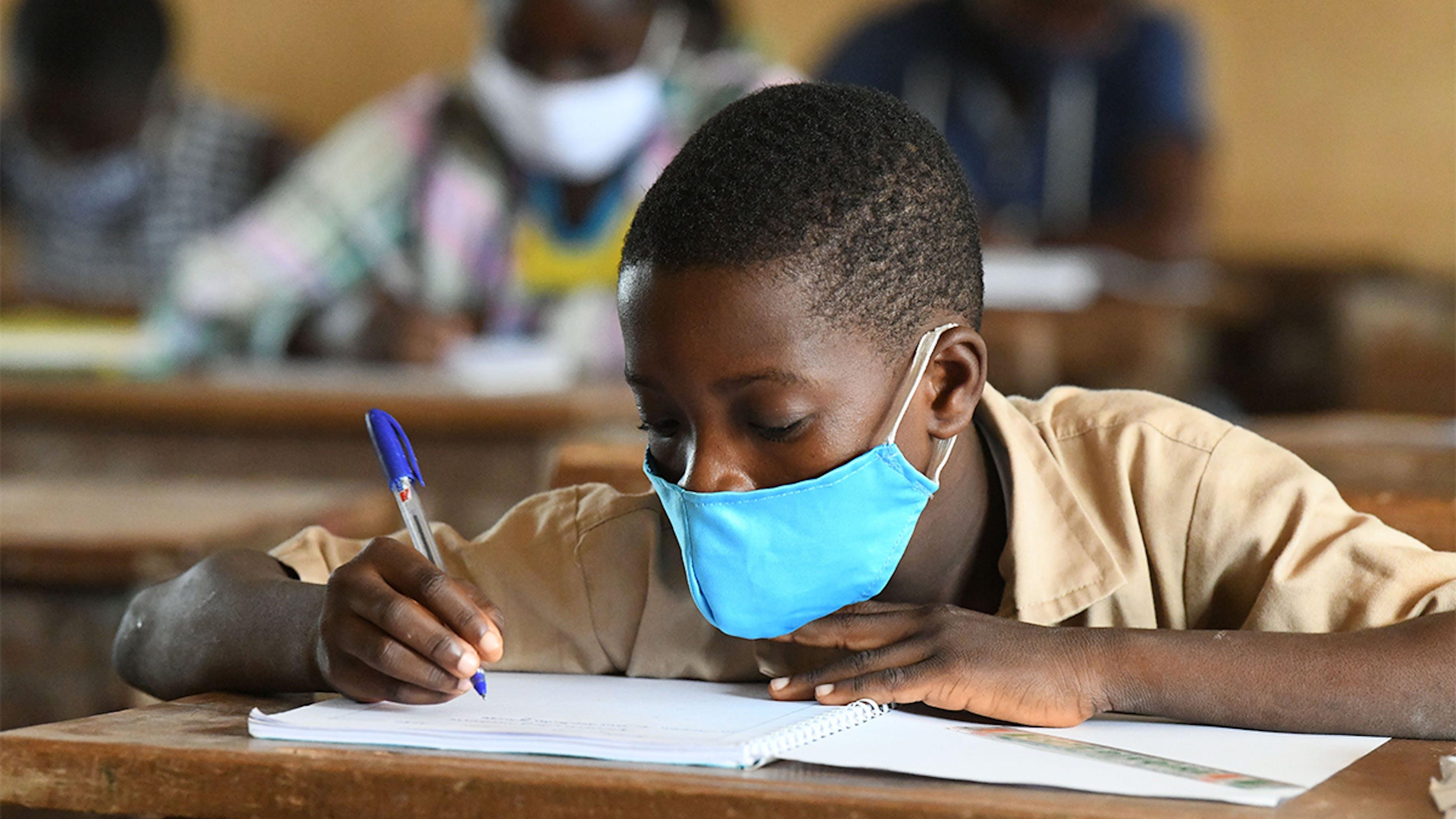 Costa d'Avorio, un ragazzo con la mascherina studia in classe.