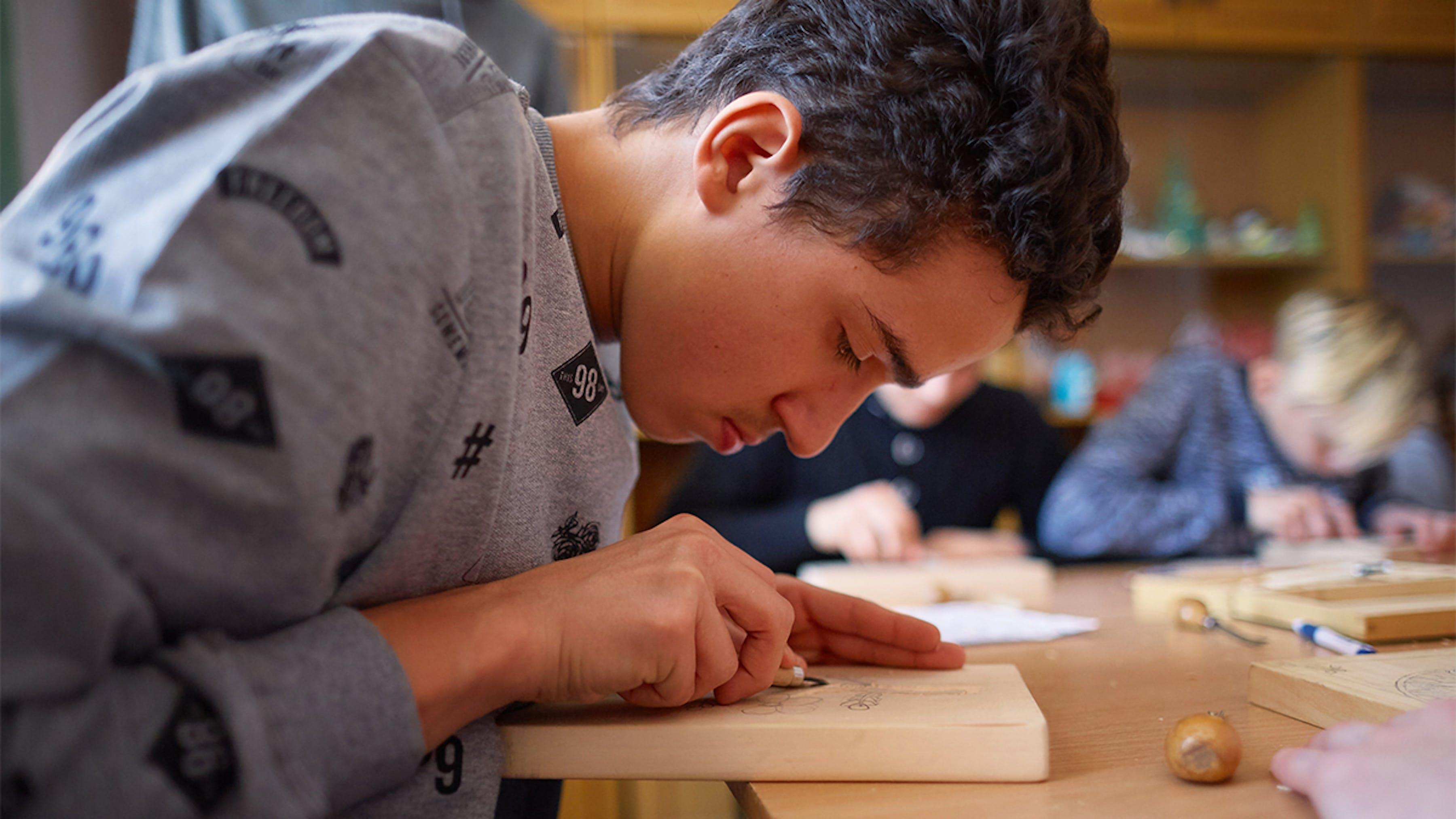 Ucraina, un ragazzo con disabilità uditive alla lezione di scultura in legno.
