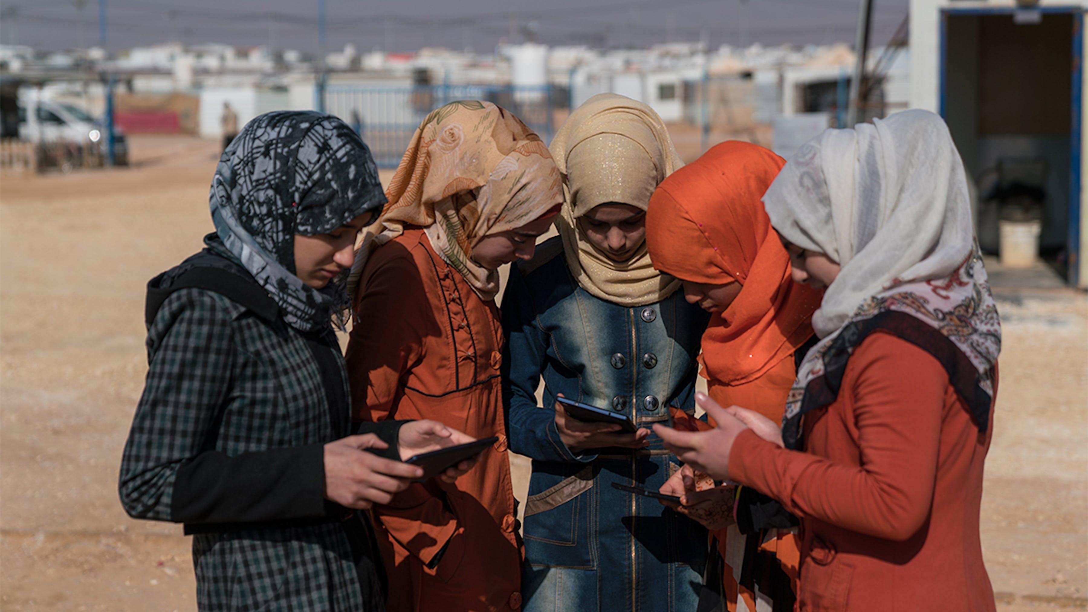 Giordania, ragazze rifugiate siriane con smartphone e tablet per l'apprendimento a distanza.